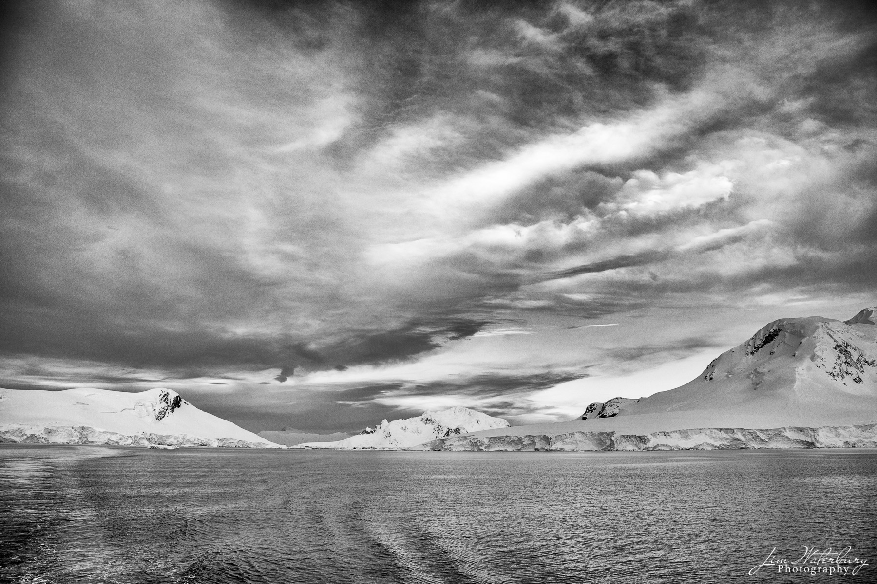 Black & white image of sea, sky and snow-covered mountains of Android Bay, Antarctica.
