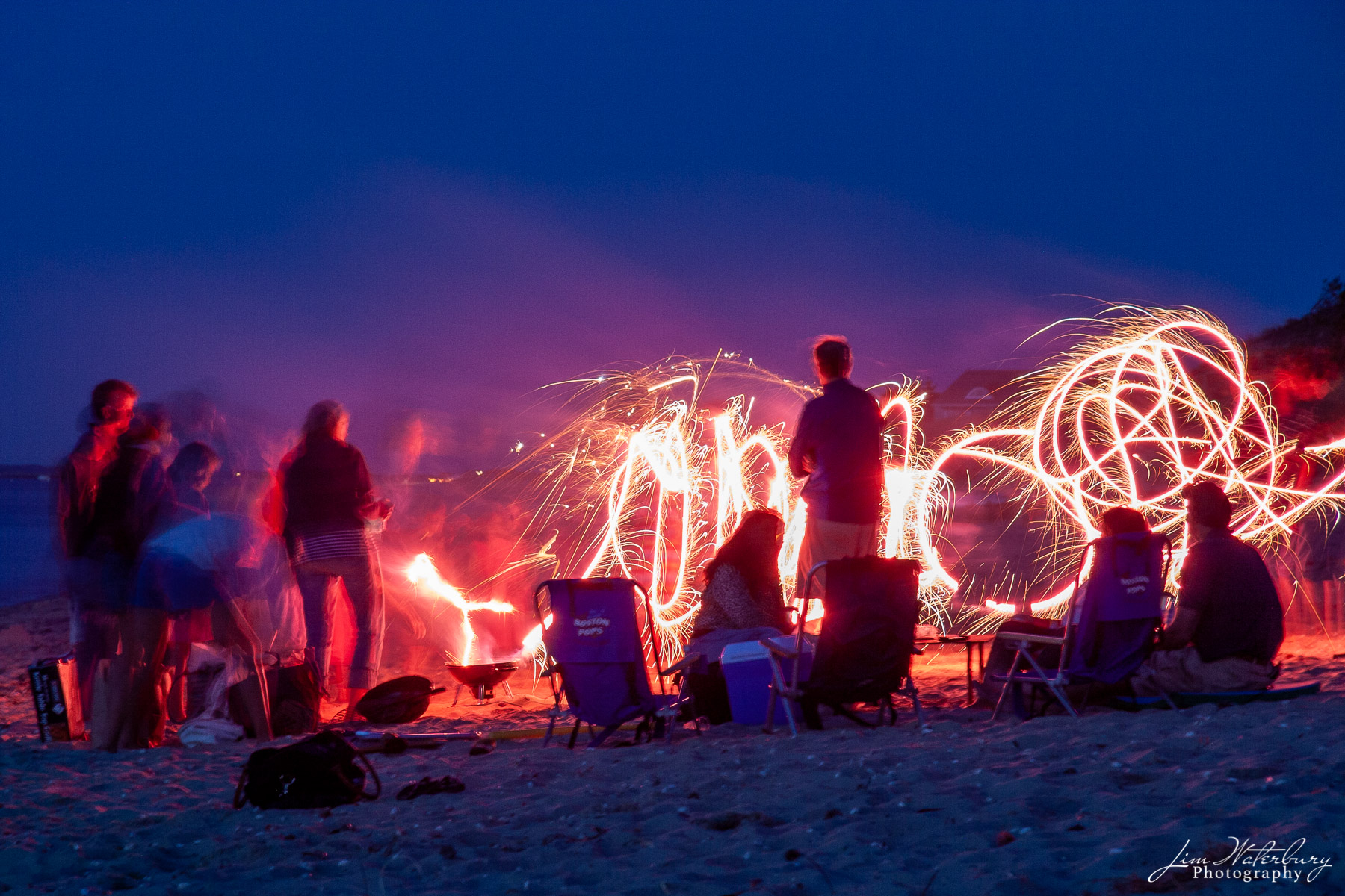 At a family picnic on a beach on the north shore of Nantucket , children draw circles of light in the night with sparklers.