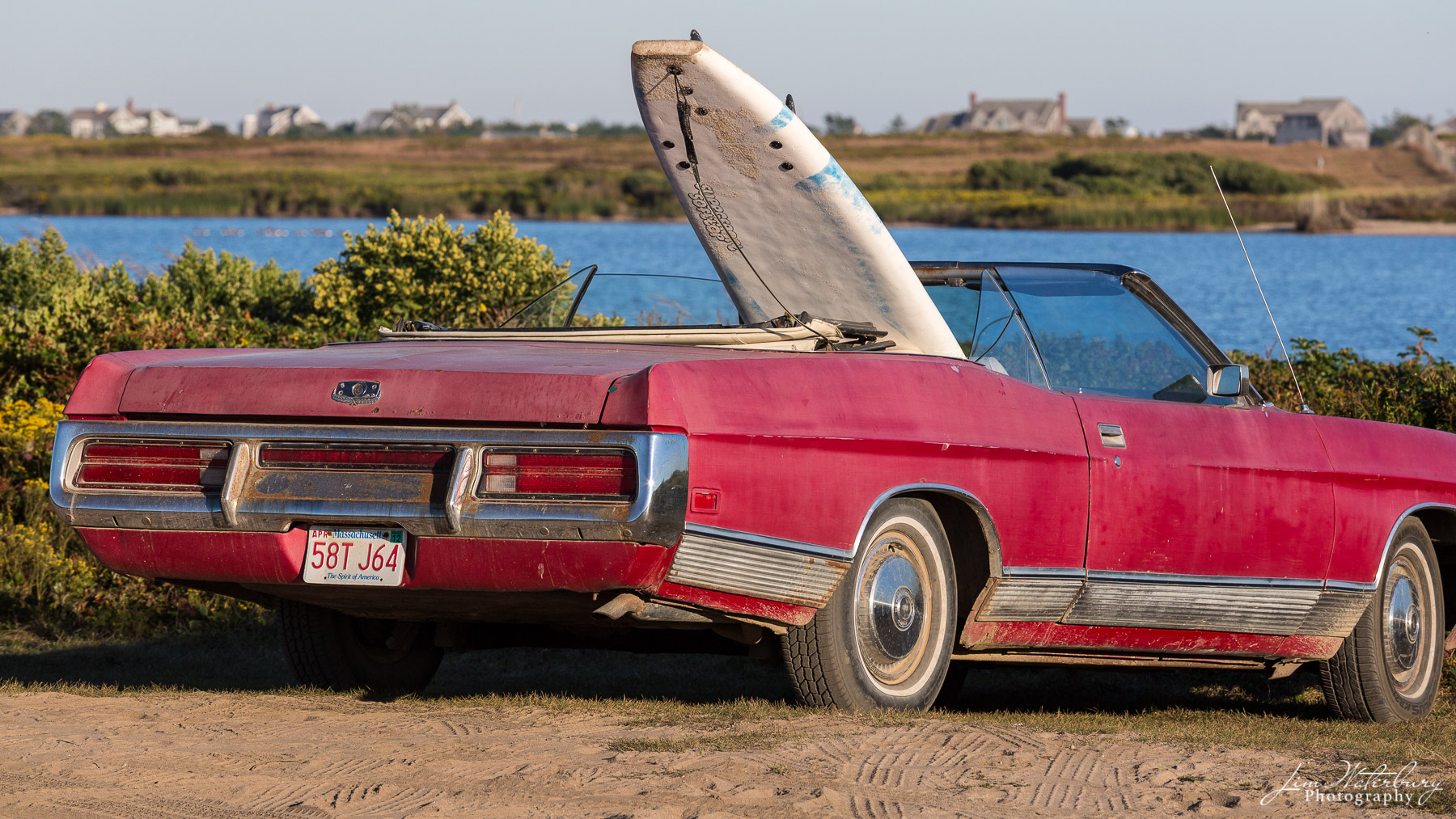 Red convertible, with surfboard in the back seat, parked in the sand at Miacomet Beach in Nantucket.