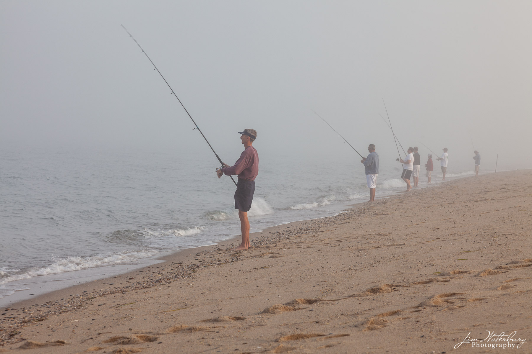 Fishermen surfcasting off the beach on Nantucket in the early morning fog.