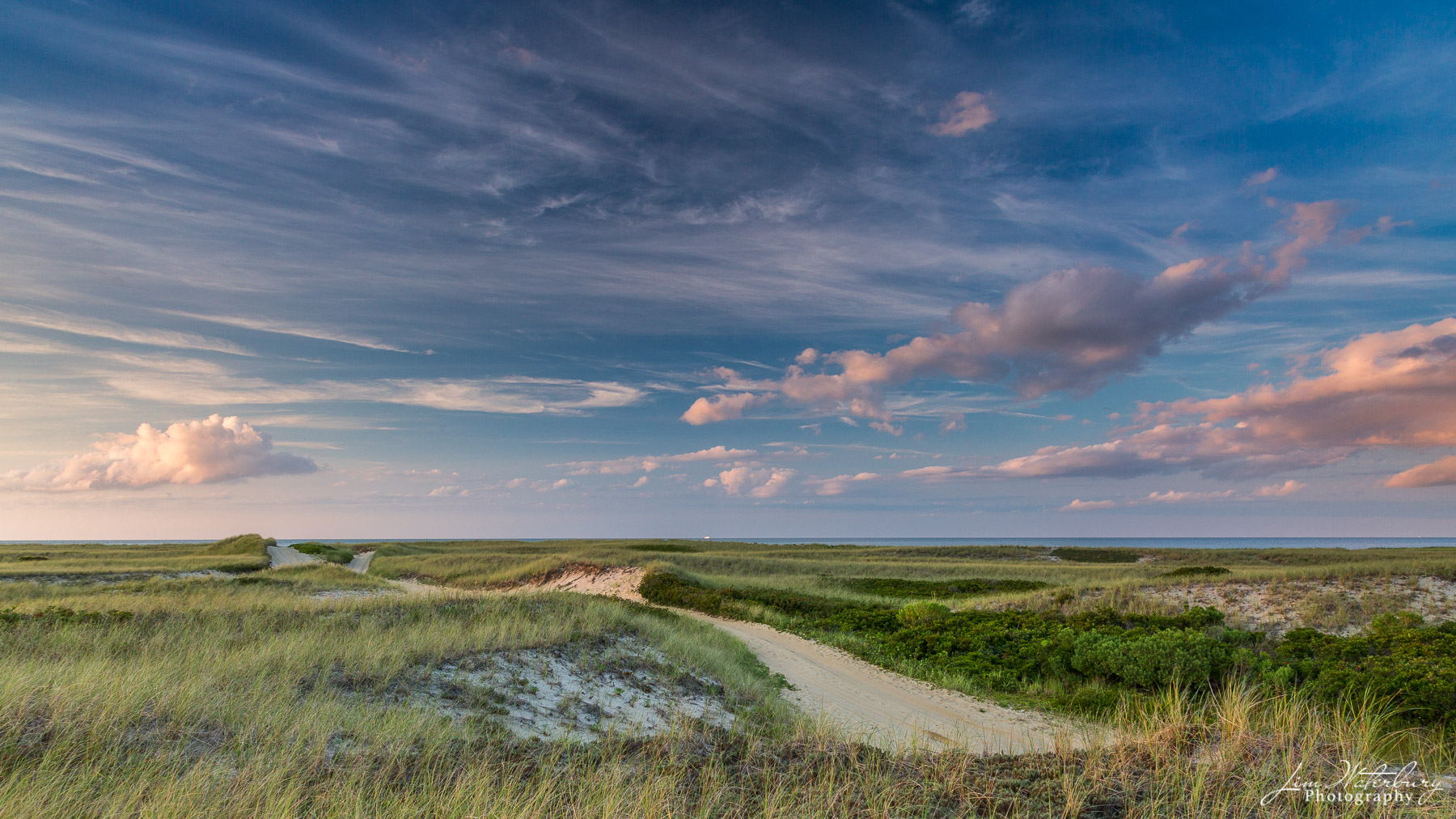 View of sand roads running through the dunes on Eel Point, Nantucket, under a late evening sky, with the ferry heading toward...