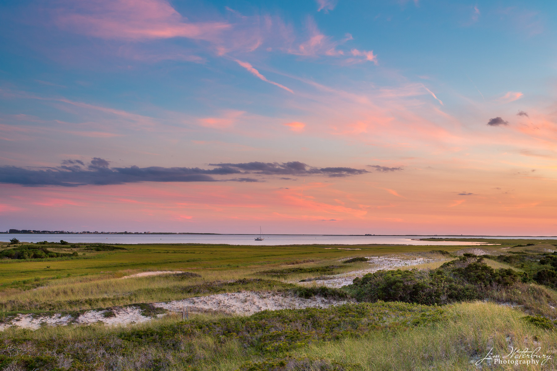 A late summer sunset reflects pink light into the clouds over Nantucket Sound, as seen from atop the sand dunes on Eel Point.