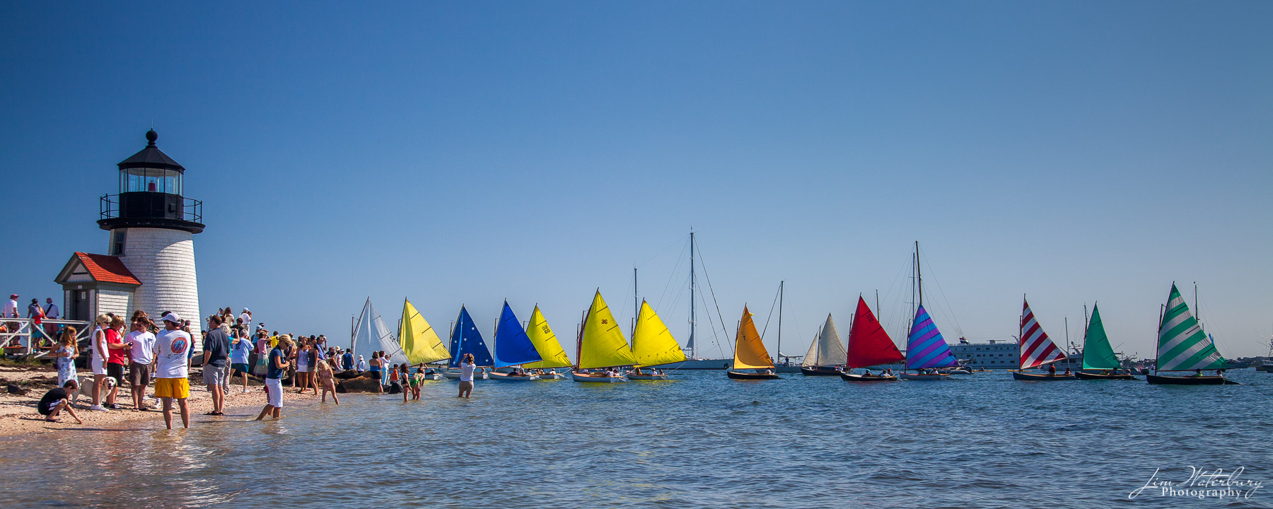Parade of the Rainbow Fleet, with their colorful sails, around Brant Point Lighthouse, Nantucket, during Race Week.