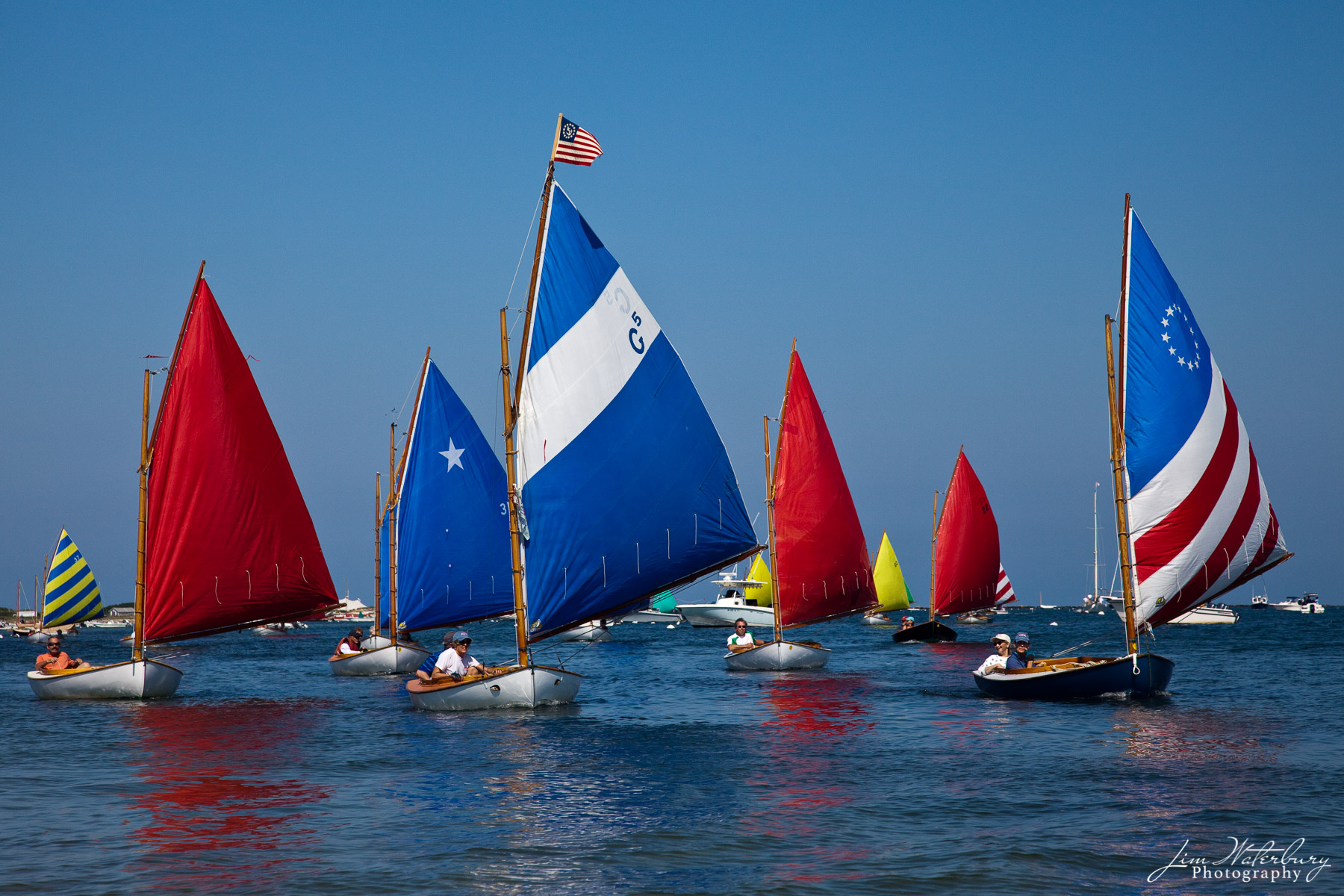Members of the Nantucket Rainbow fleet, with their colorful red, white and blue sails, kick off the final day of sailing at the...