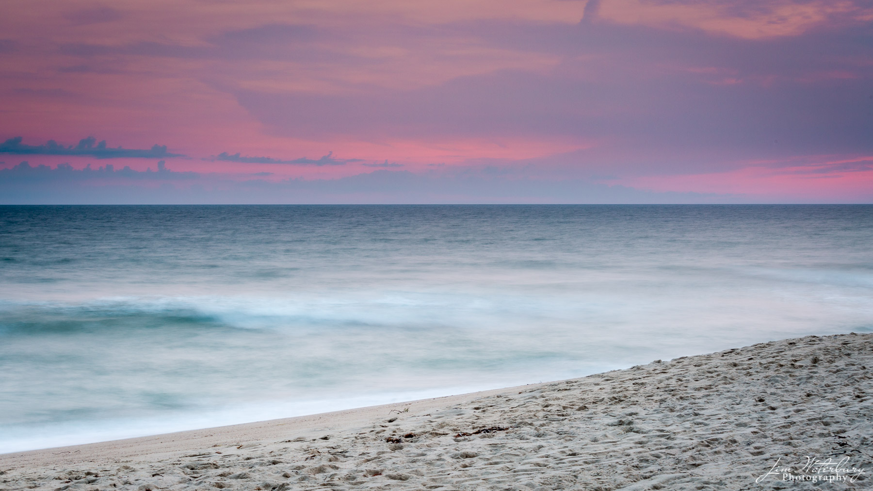 The sky lights up in hues of pink and purple over the ocean at sunset, near Lady's Beach, Nantucket.