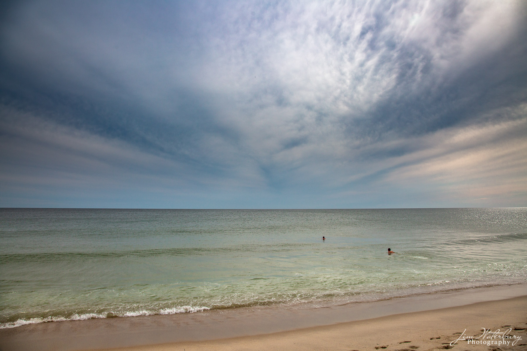 A calm ocean attracts two swimmers under a stormy late afternoon sky in Nantucket.