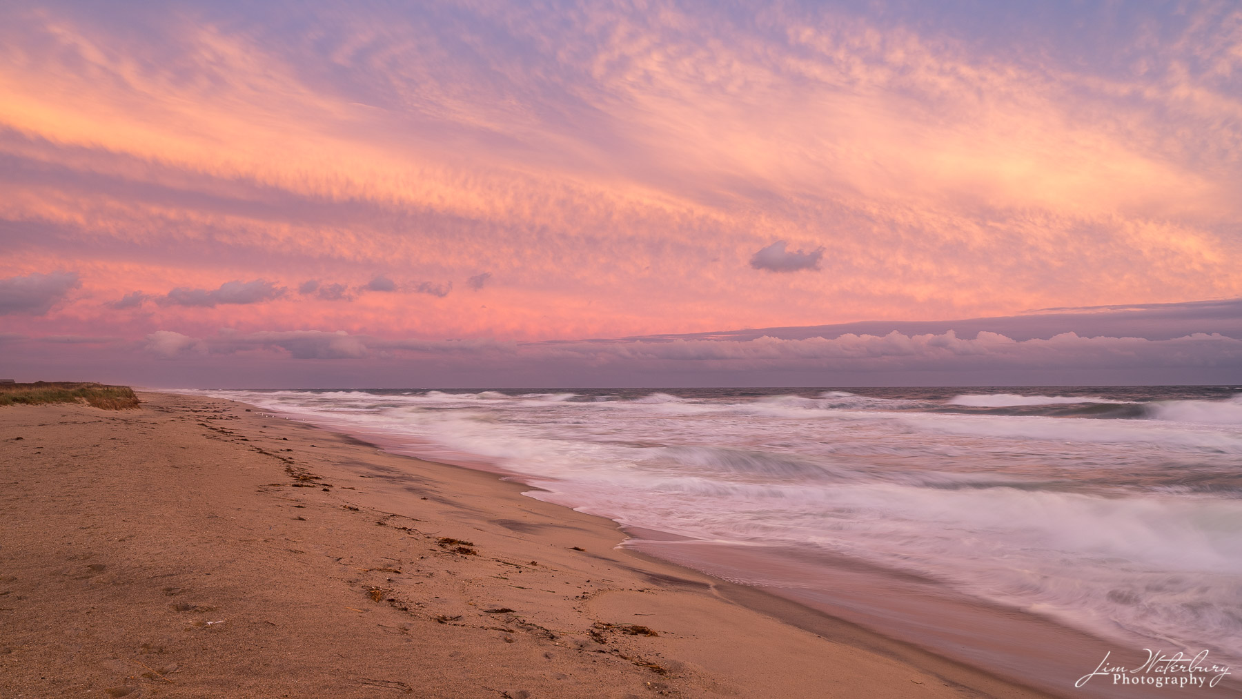Rolling waves from the Atlantic Ocean approach the shore under wispy pink clouds above.