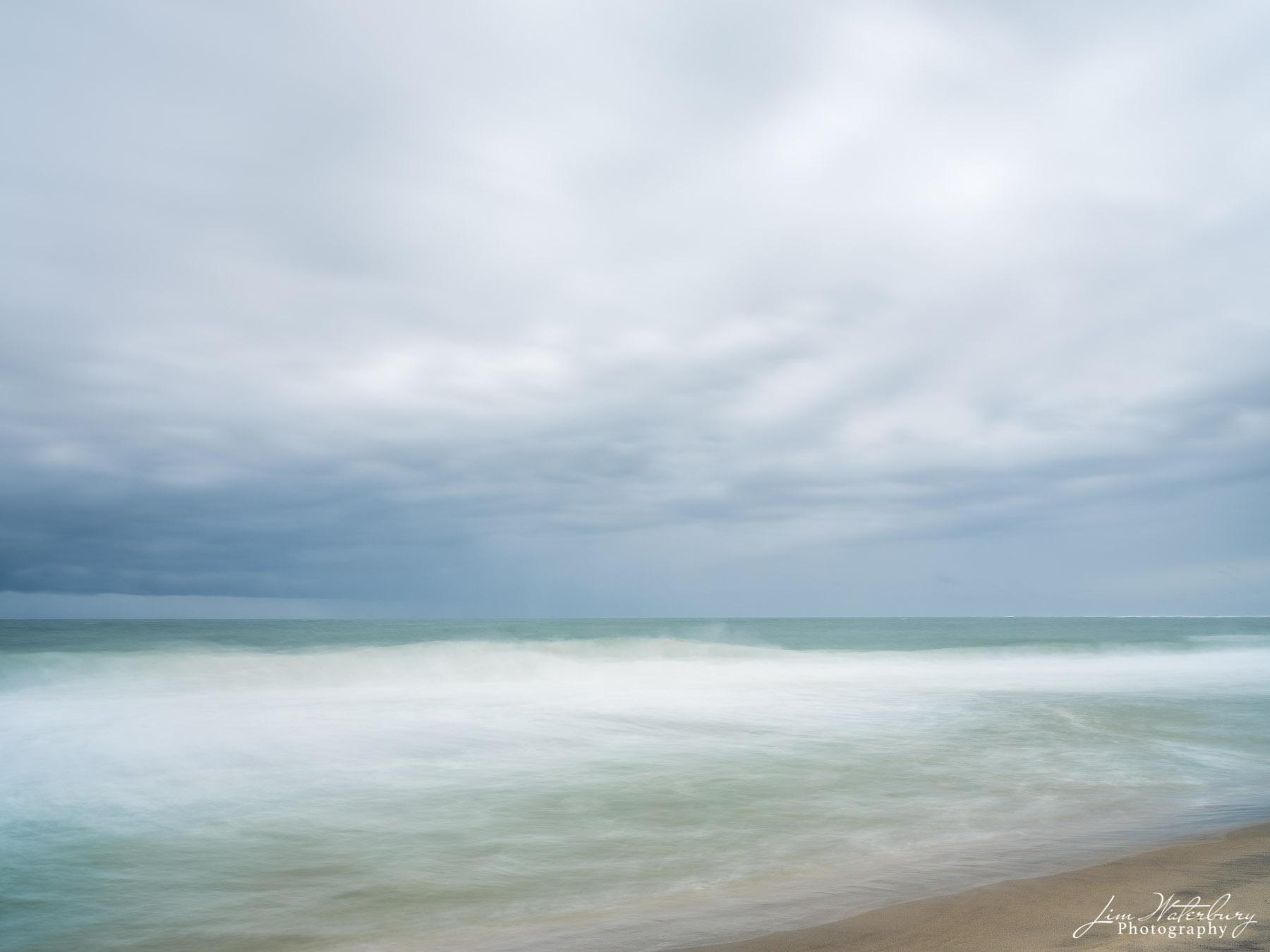 A long exposure blurs ocean and clouds off Cisco Beach, Nantucket.