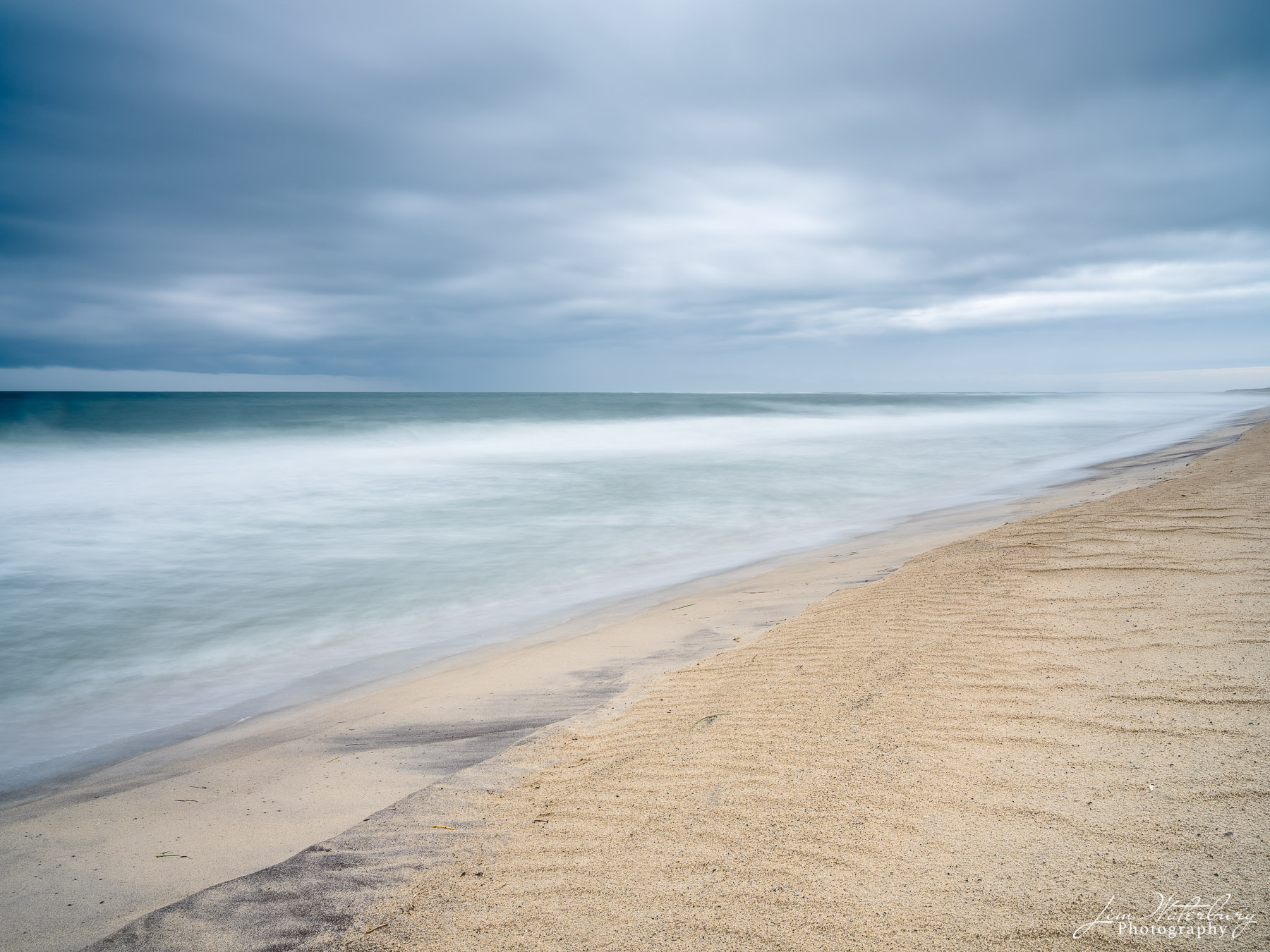 A long exposure blurs the water and shows movement in the gray skies over the ocean in Nantucket, MA.