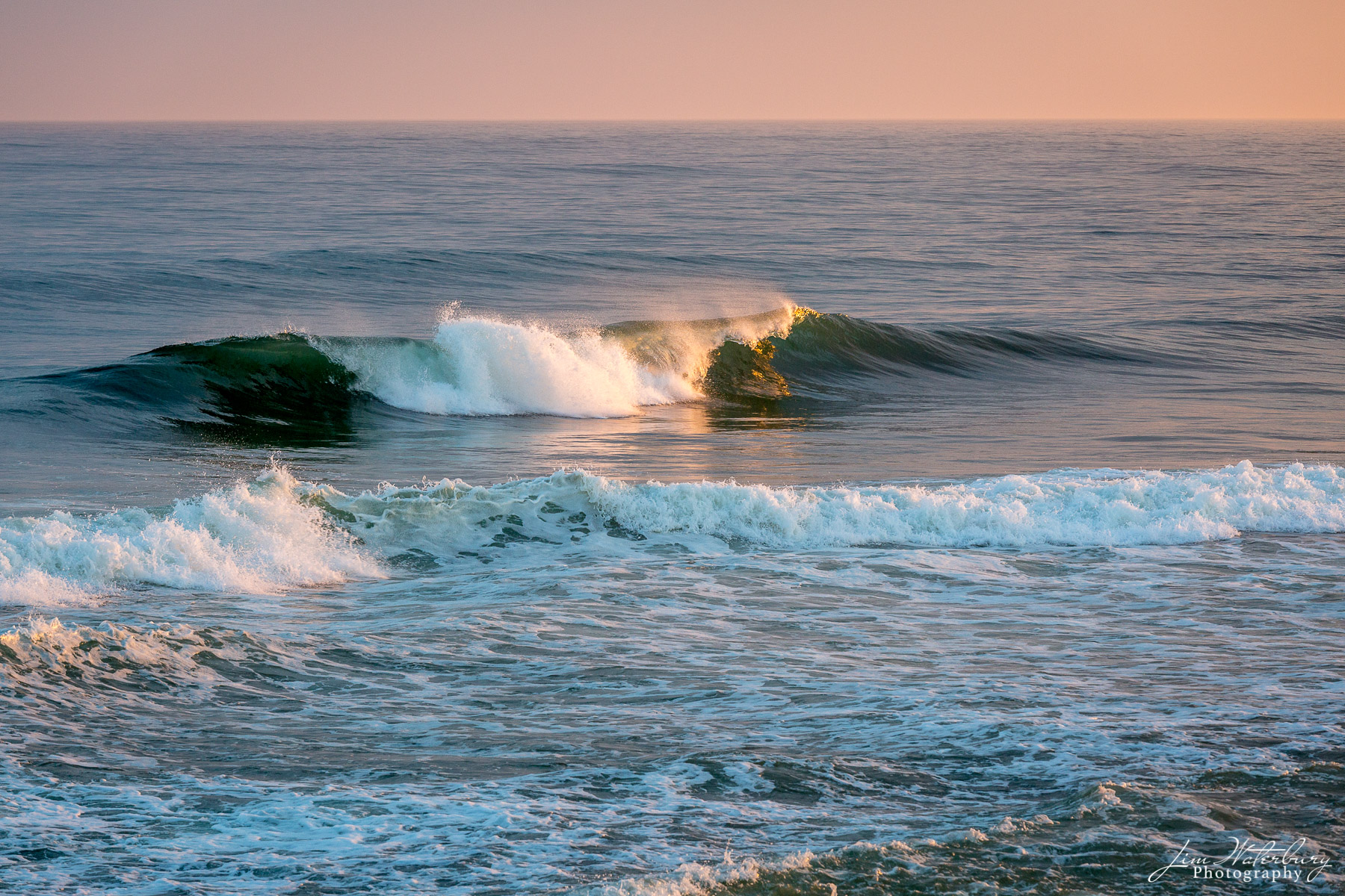 A breaking wave catches the light of the setting sun at Cisco Beach, Nantucket.