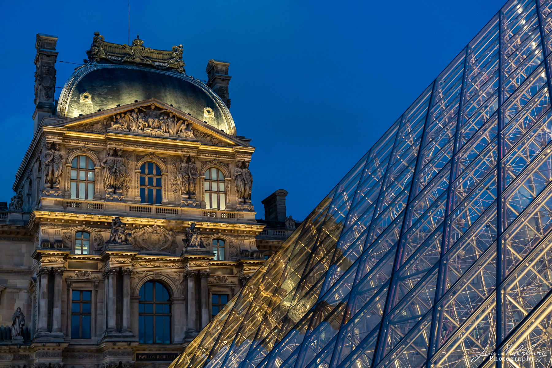 Photographed at night, this image contrasts the windows of the magnificent, baroque-style Palais du Louvre, originally built...
