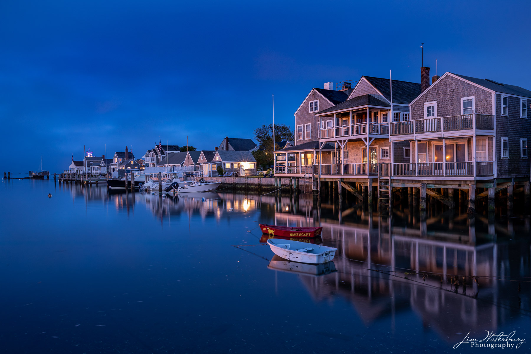Night image of Easy Street Boat Basin, and reflections of the cottages of Old North Wharf on the calm waters below, with the...