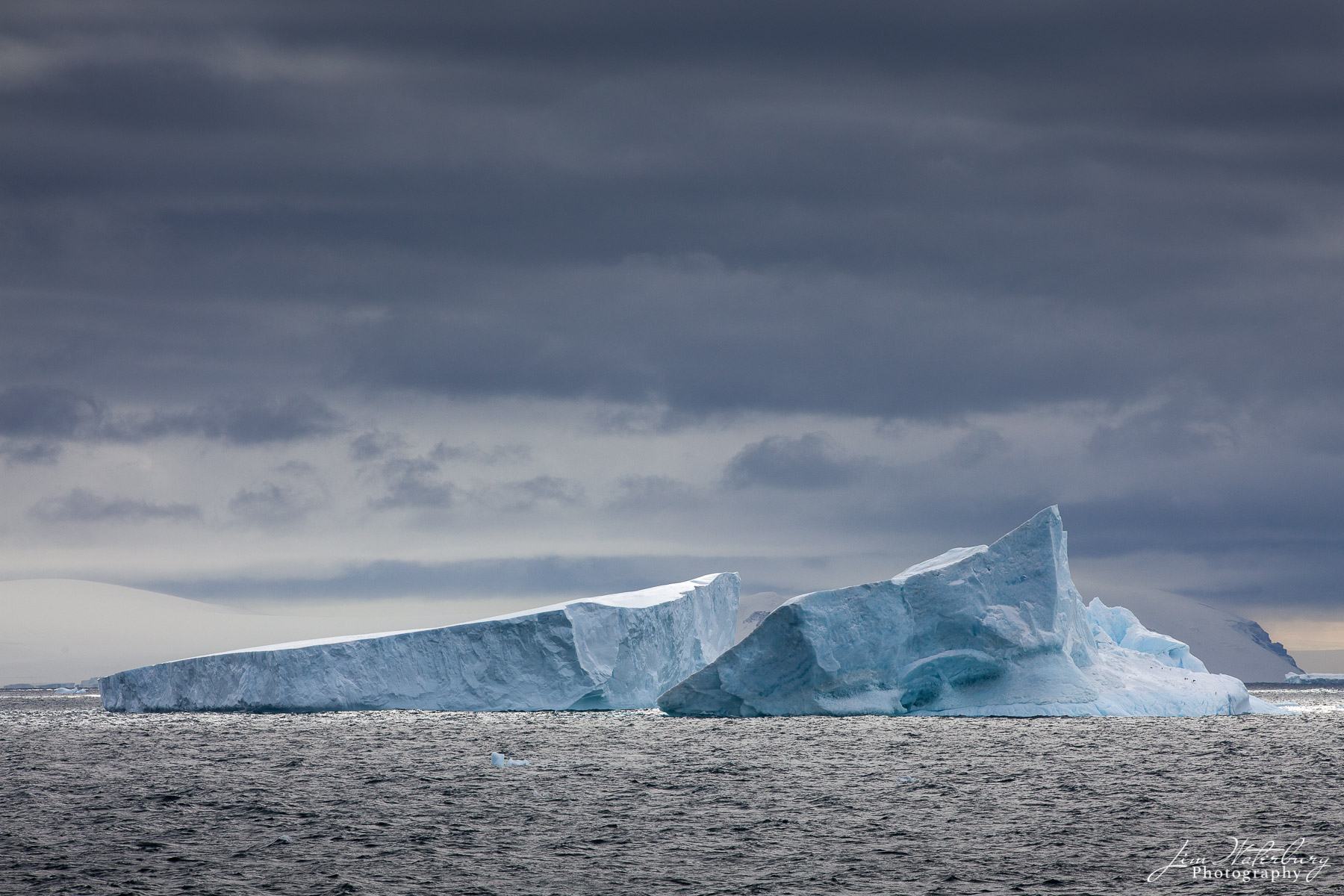 Image of a large iceberg that appears to have broken in two and is now floating in the Antarctic Sound.