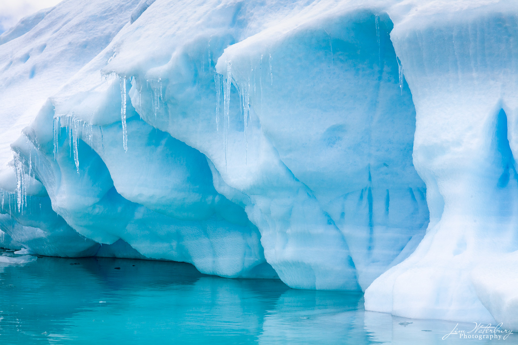 Leaning pillars and icicles on the edge of an iceberg in the Lemaire Channel in Antarctica reflect in the crystal-clear turquoise...