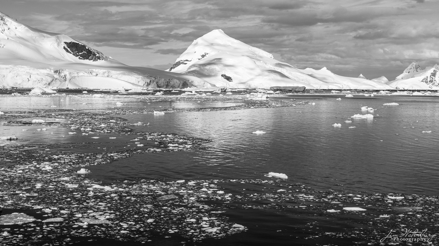 Black & white image of Paradise Harbour, with snow-covered mountains reflected in the surrounding sea, dotted with pieces of...