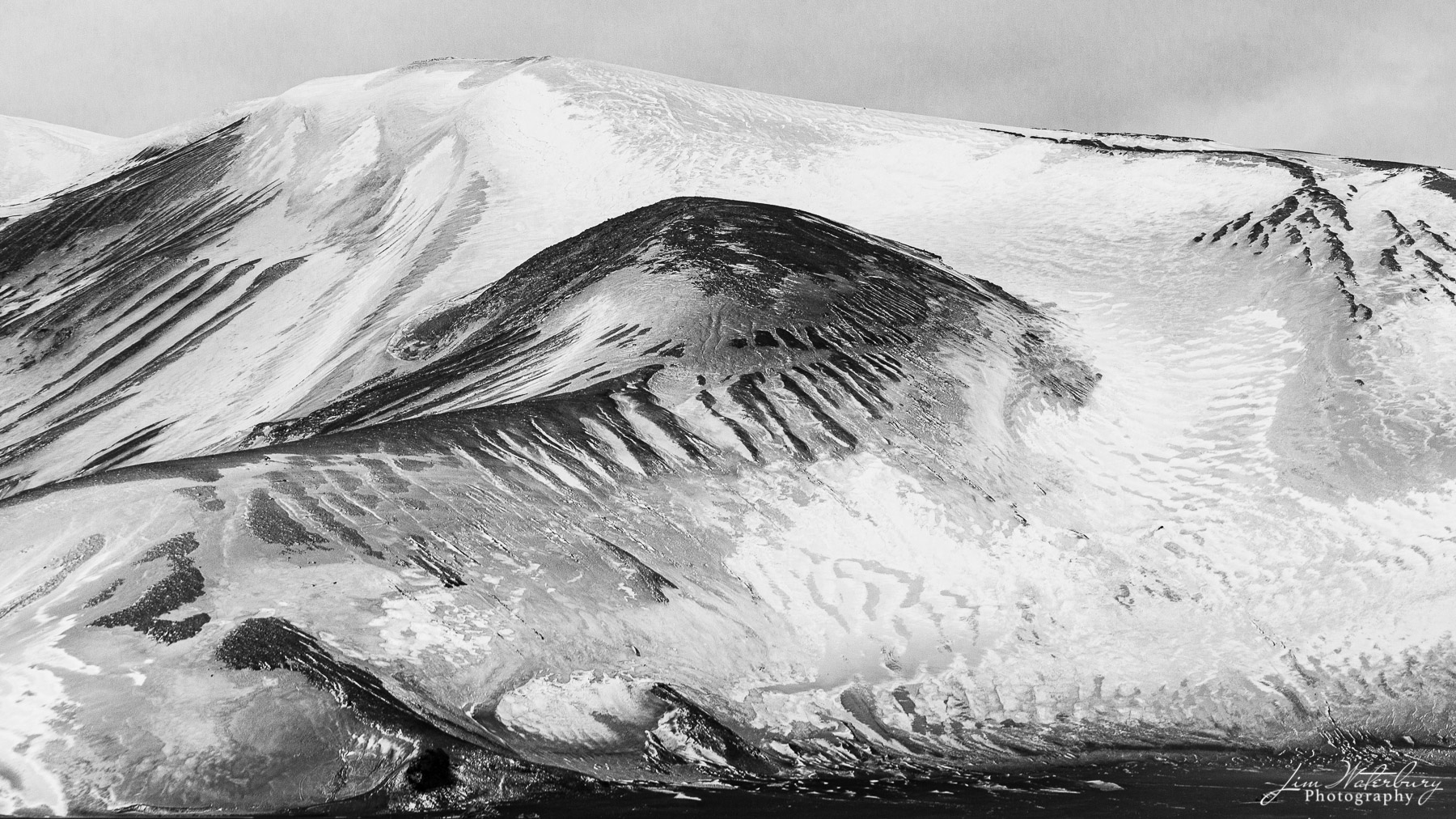 Patterns of snow and contrasting lava base at Deception island, Antarctica.