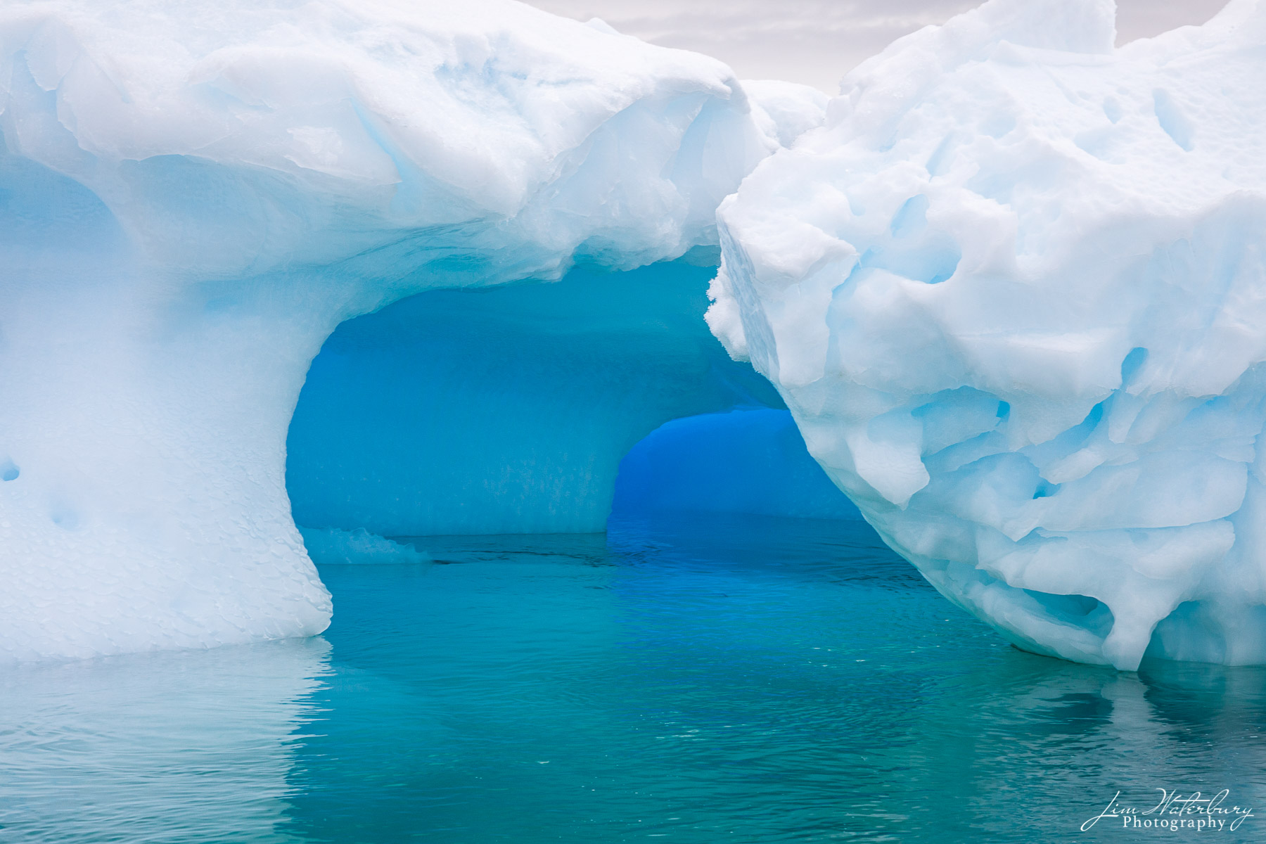 A tunnel, formed on the bottom of an iceberg floating in the Lemaire Channel, shows striking shades of aqua and blue -- in the...