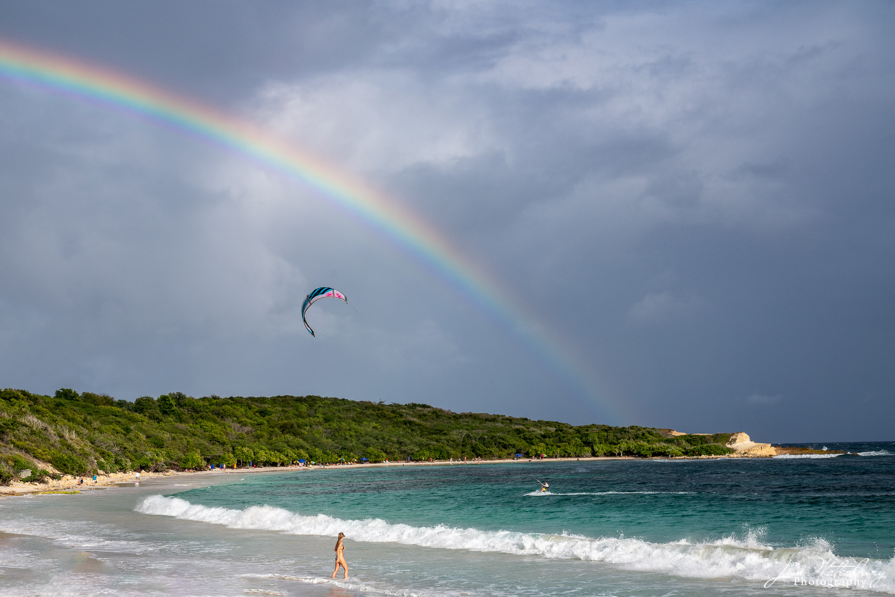 A late afternoon scene at Half Moon Bay in Antigua shows a rainbow against dark rain clouds, a woman about to enter the ocean...