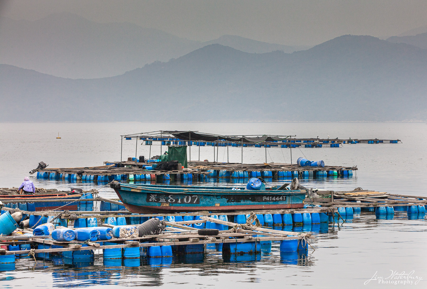 A floating fish farm at Tap Mun (Grass Island), Hong Kong, against a backdrop of hazy mountains in the distance. Tap Mun is located...