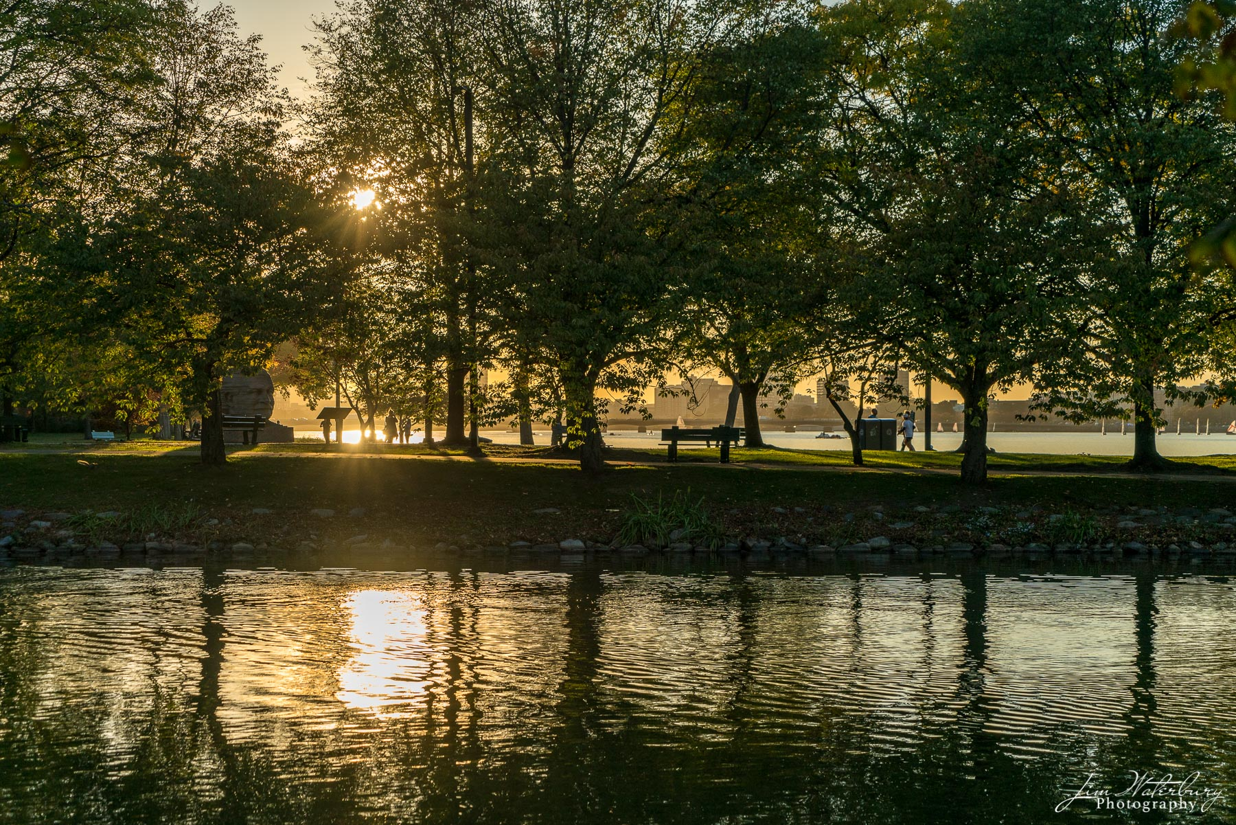 The late afternoon sun shines its warm light across the waters of the Charles River in Boston.