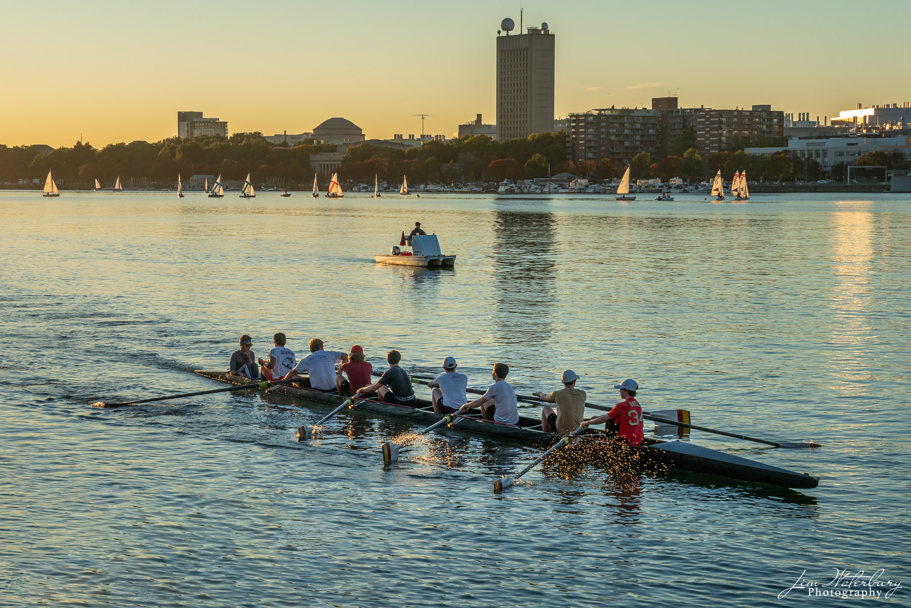 Boats of various types and sizes practice in the late afternoon sunlight on the Charles River in Boston.