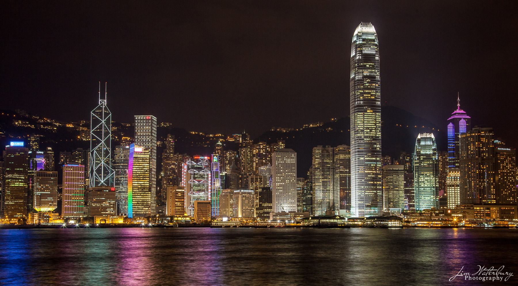 View of the skyscrapers of Hong Kong, illuminated at night, from a boat on Victoria Harbor.