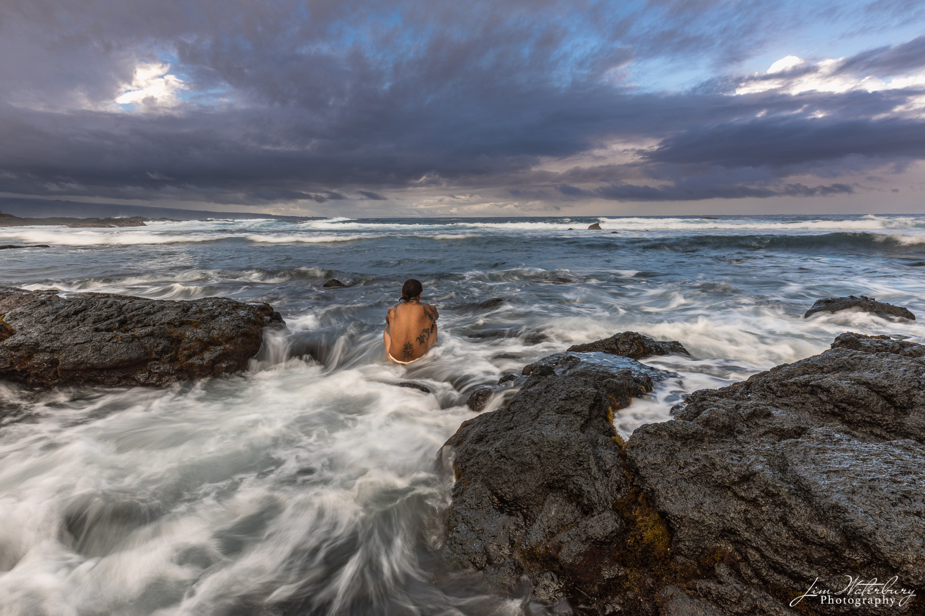 A local Hawaian looks out into the vastness of the Pacific Ocean, from the rocky shores near Hilo, on the Big Island of Hawaii...