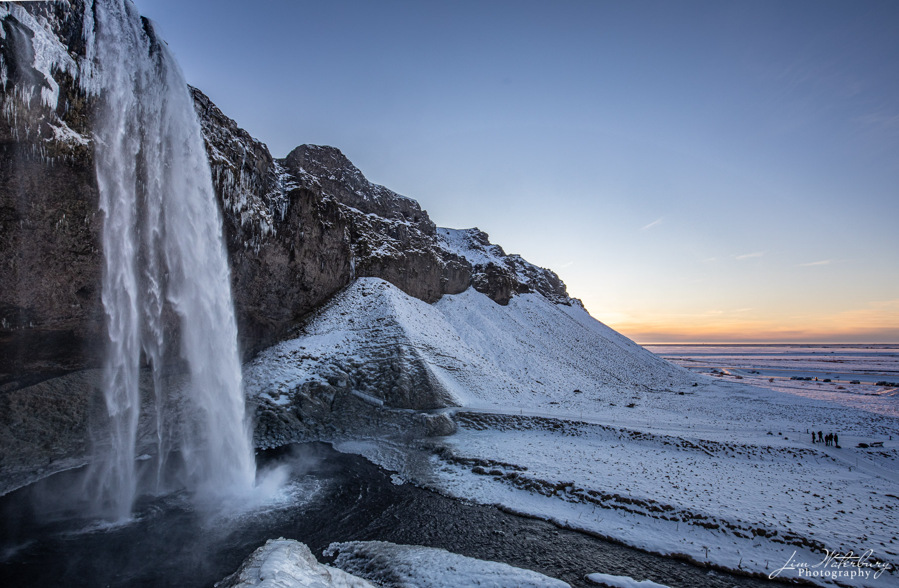 Seljalandsfoss waterfall accents a snow-covered winter landscape in Southern Iceland at sunset.