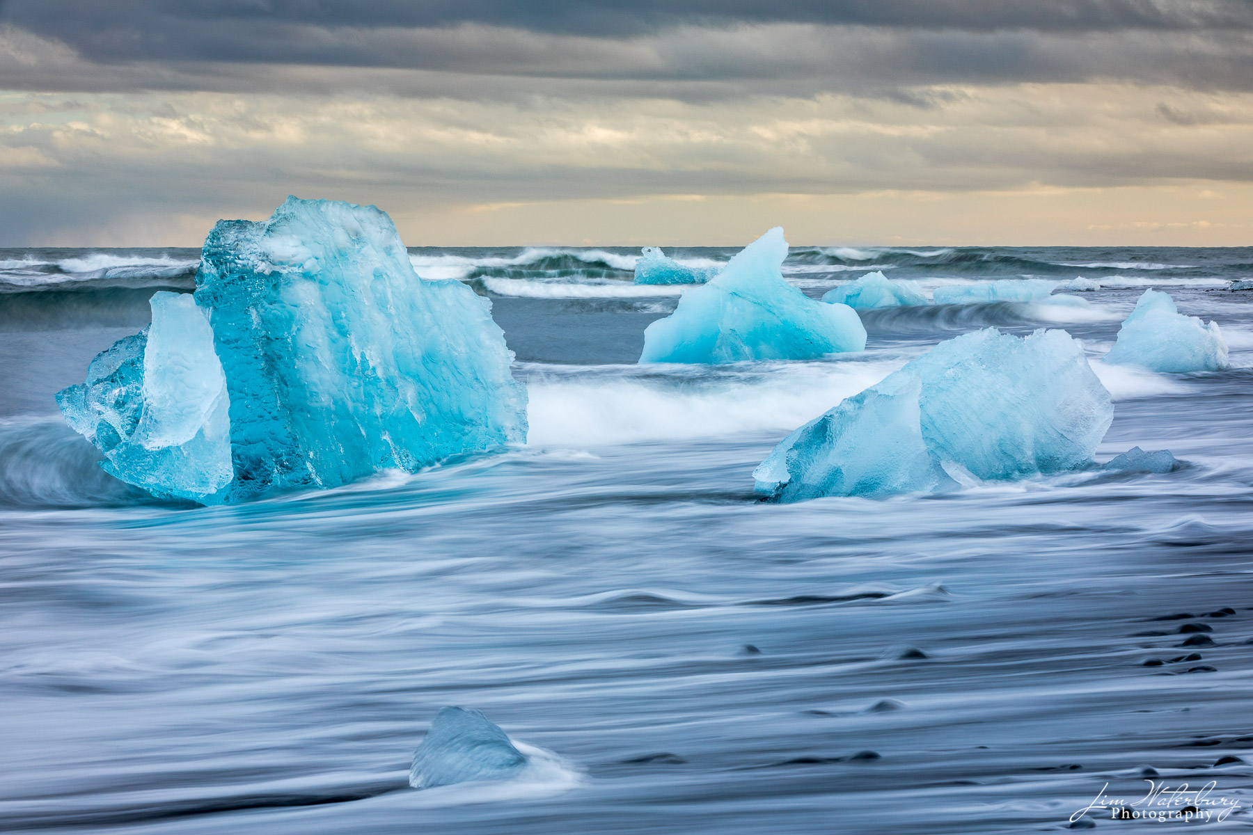 Small icebergs, with their vibrant blue hue, are anchored on the black sand beach of Fellsfjara, and battered by an endless stream...