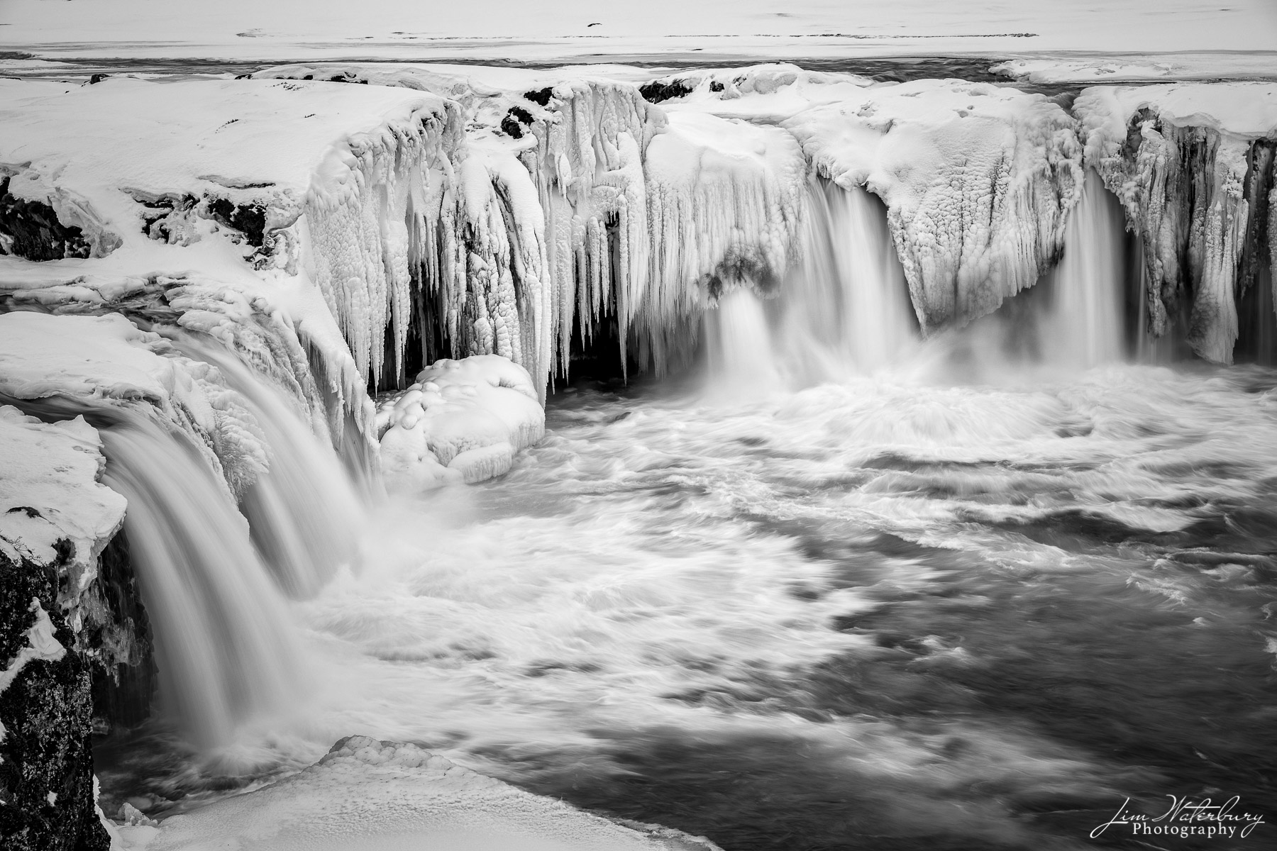 "Black & white image of the partly frozen Godafoss waterfall (""Waterfall of the Gods"") in Northern Iceland in winter."