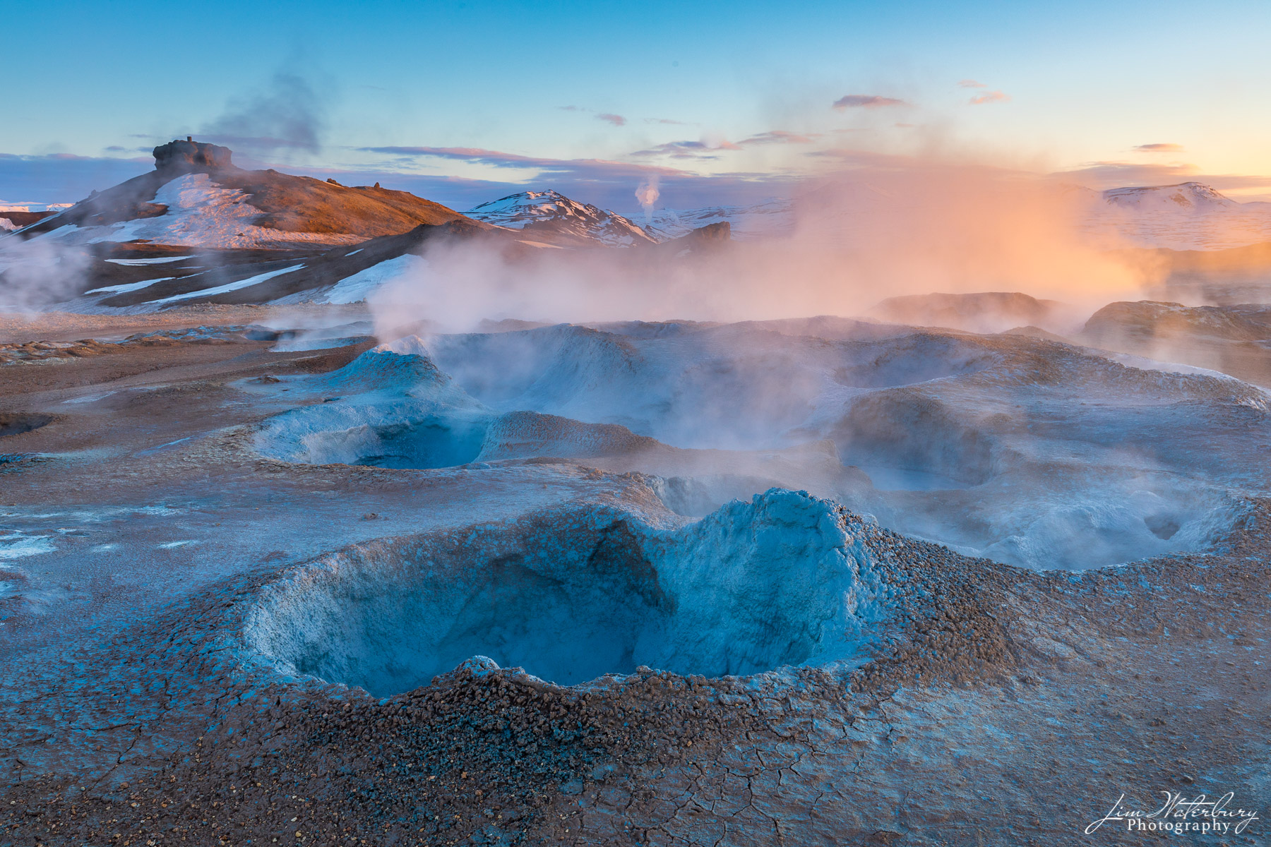 The soft, warm light of sunrise illuminates the smoking fumaroles and blue-rimmed boiling mud pots of the Namaskard geothermal...