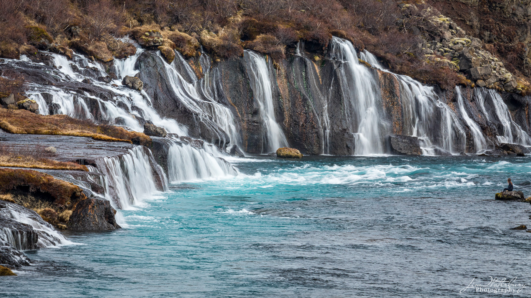 A young girl sits on an outcrop of rock to take in the natural beauty of the Hraunfossar waterfalls, as glacial melt waters cascade...