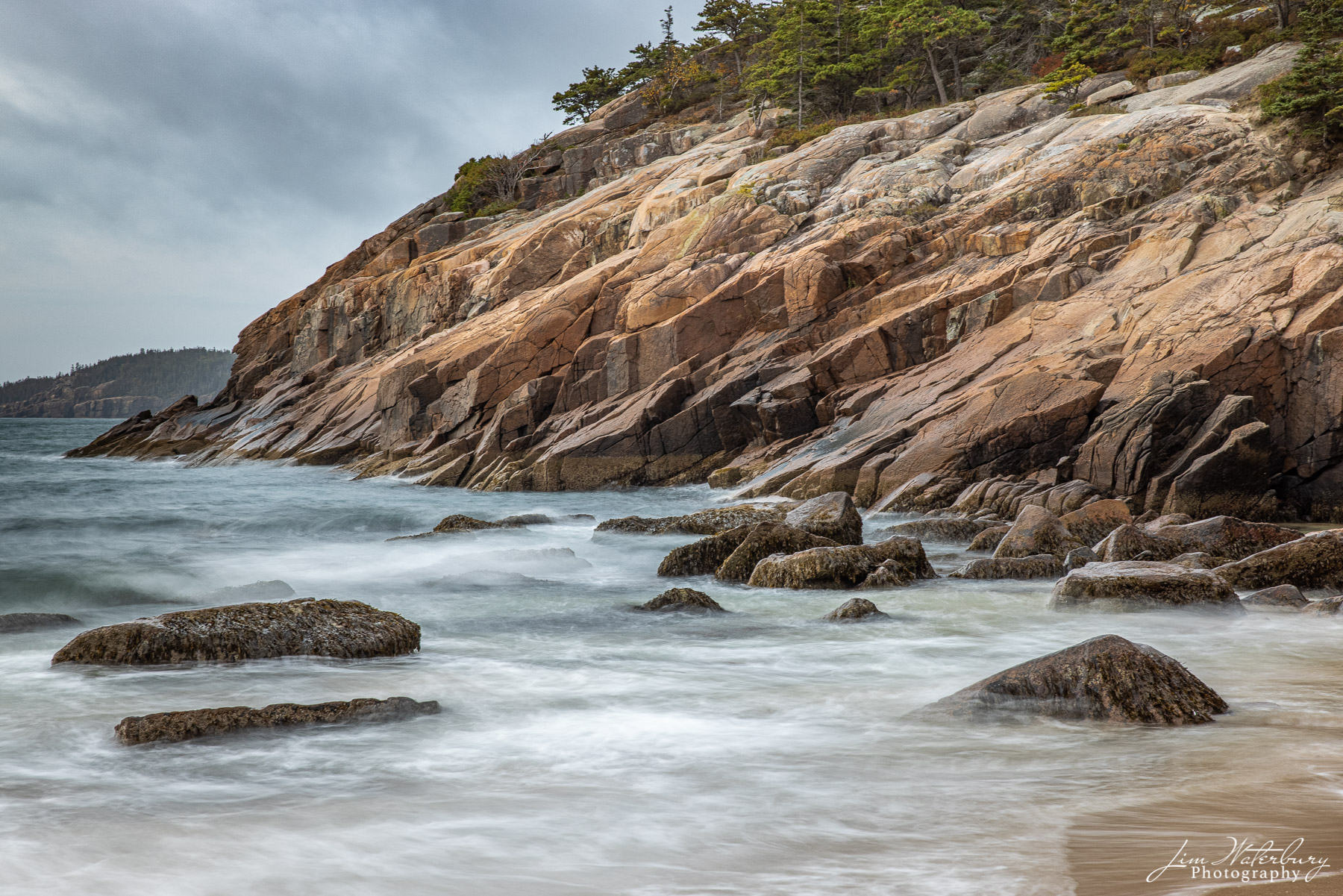The rocky shore at Sand Beach, Acadia National Park, bathed by the warm light of sunrise.