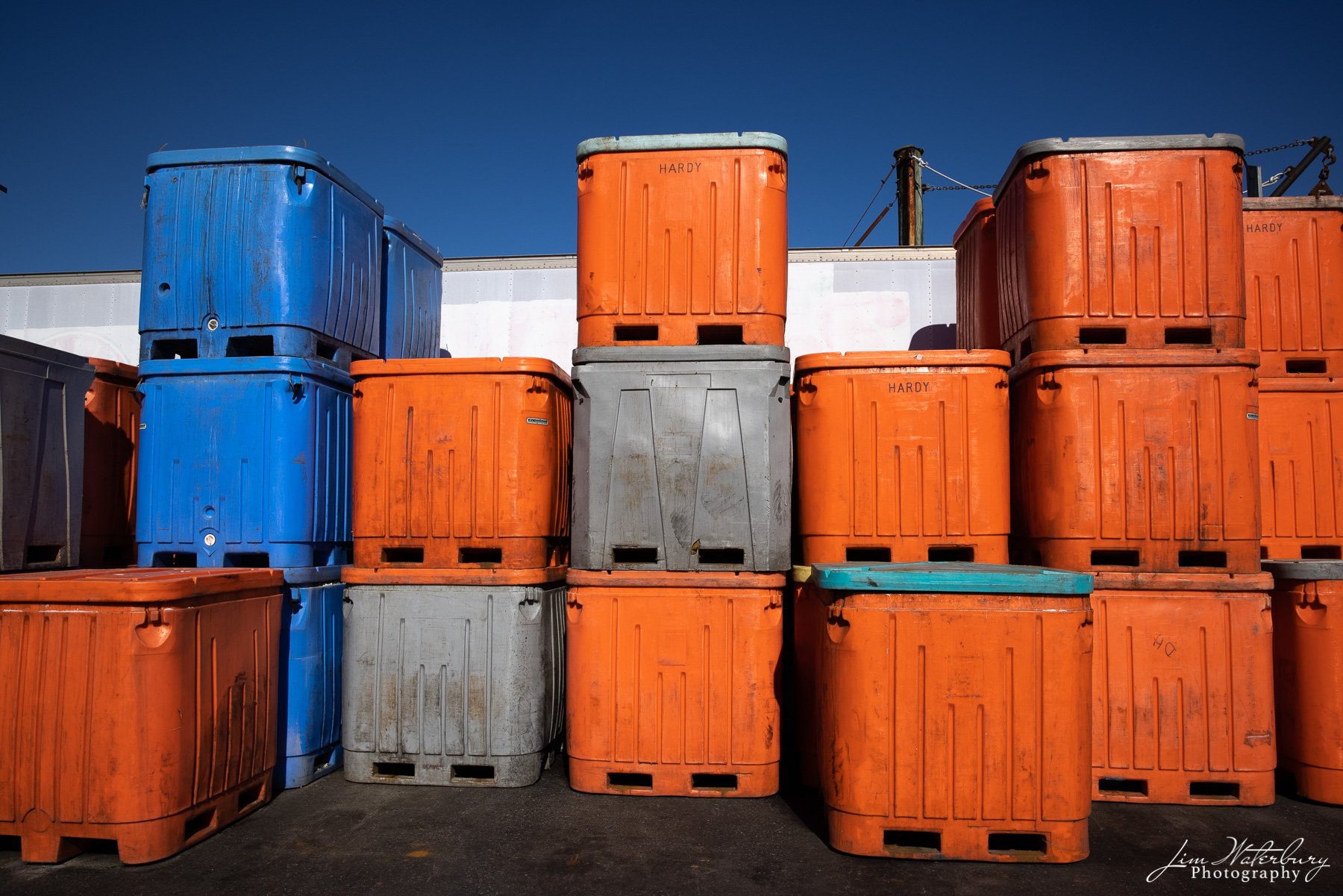 Brightly colored orange and blue storage containers on the dock at the port in Stonington, Maine.