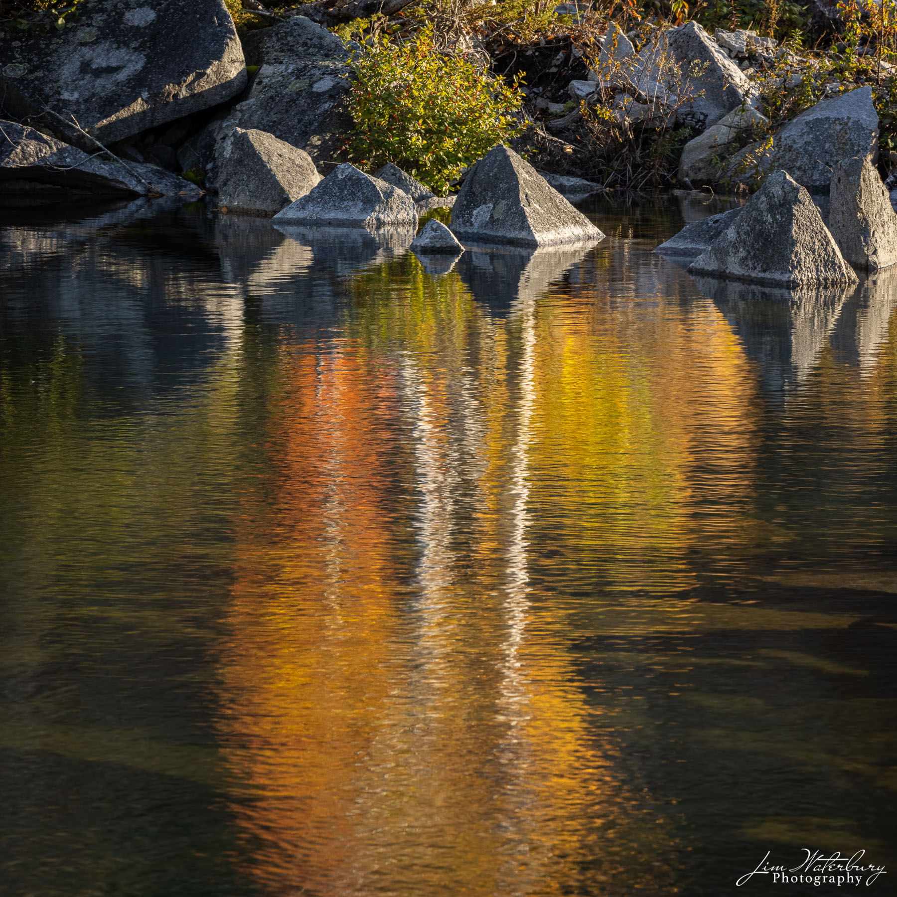 Fall colors reflect in the deep waters of Long Cove Quarry, Maine