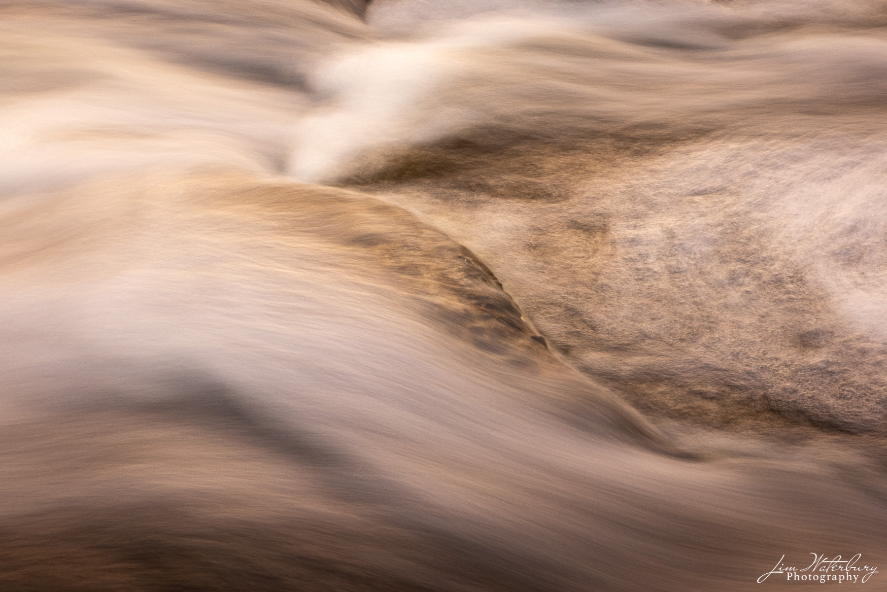 Abstract of water rushing over rocks at Goose River, photographed in the late afternoon light, from the Goose River Peace Corps...