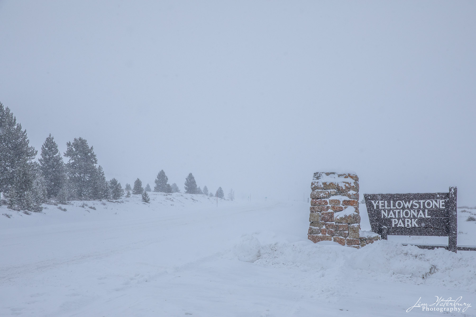 Sign signaling the entrance to Yellowstone National Park en route from Bozeman, MT, in white-out conditions.