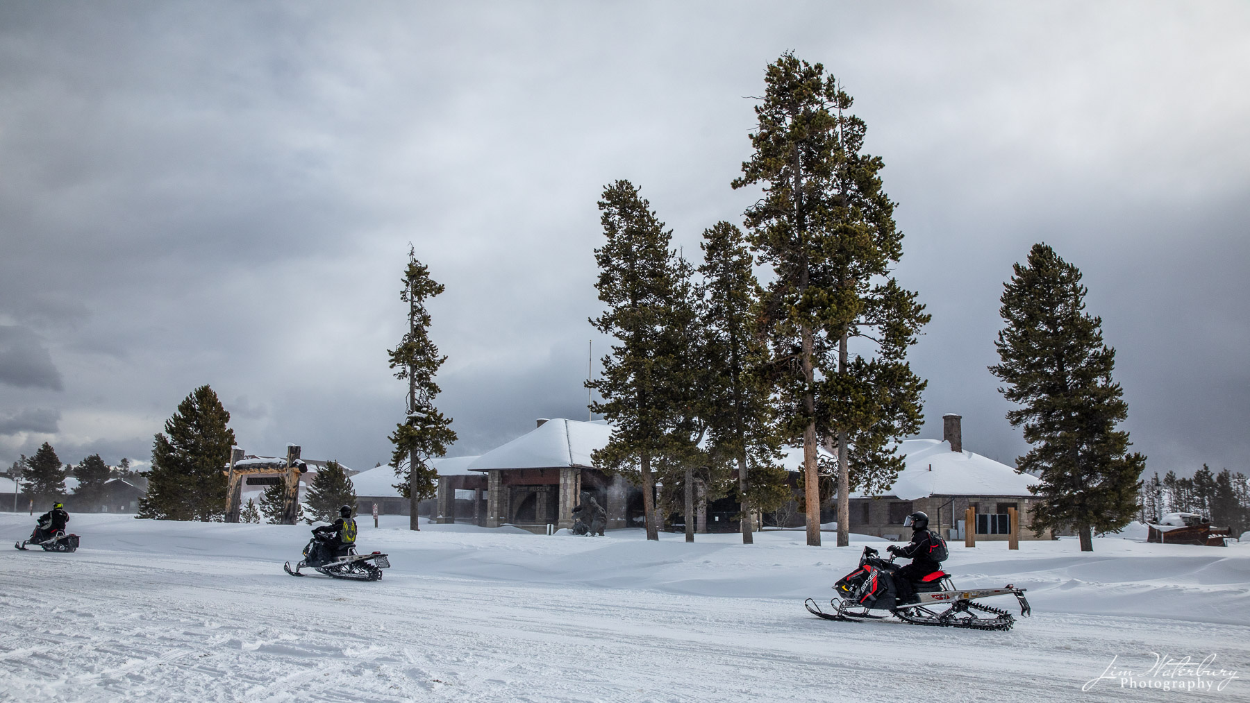 Snowmobiles parade down one of the main streets in West Yellowstone, MT in mid-winter.