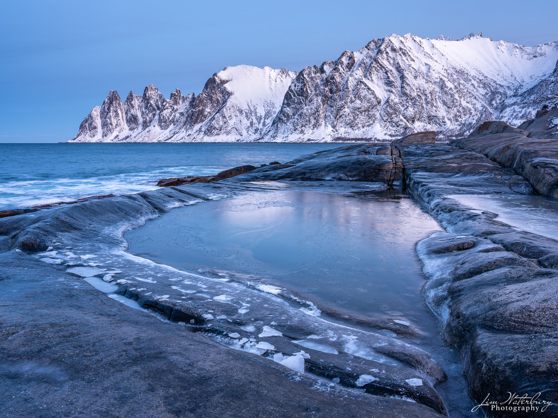 Early morning view of snow-covered mountains from a rocky point across the fjord, taken near Tungeneset, on the island of Senja...