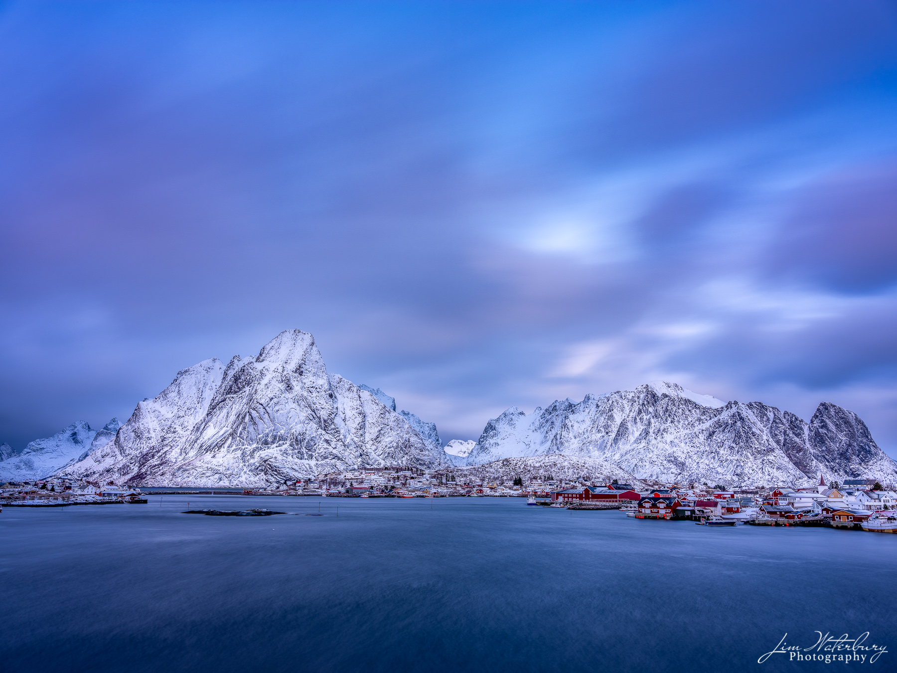 Winter view of the fishing village of Reine, with its traditional fishing cottages, at dusk.