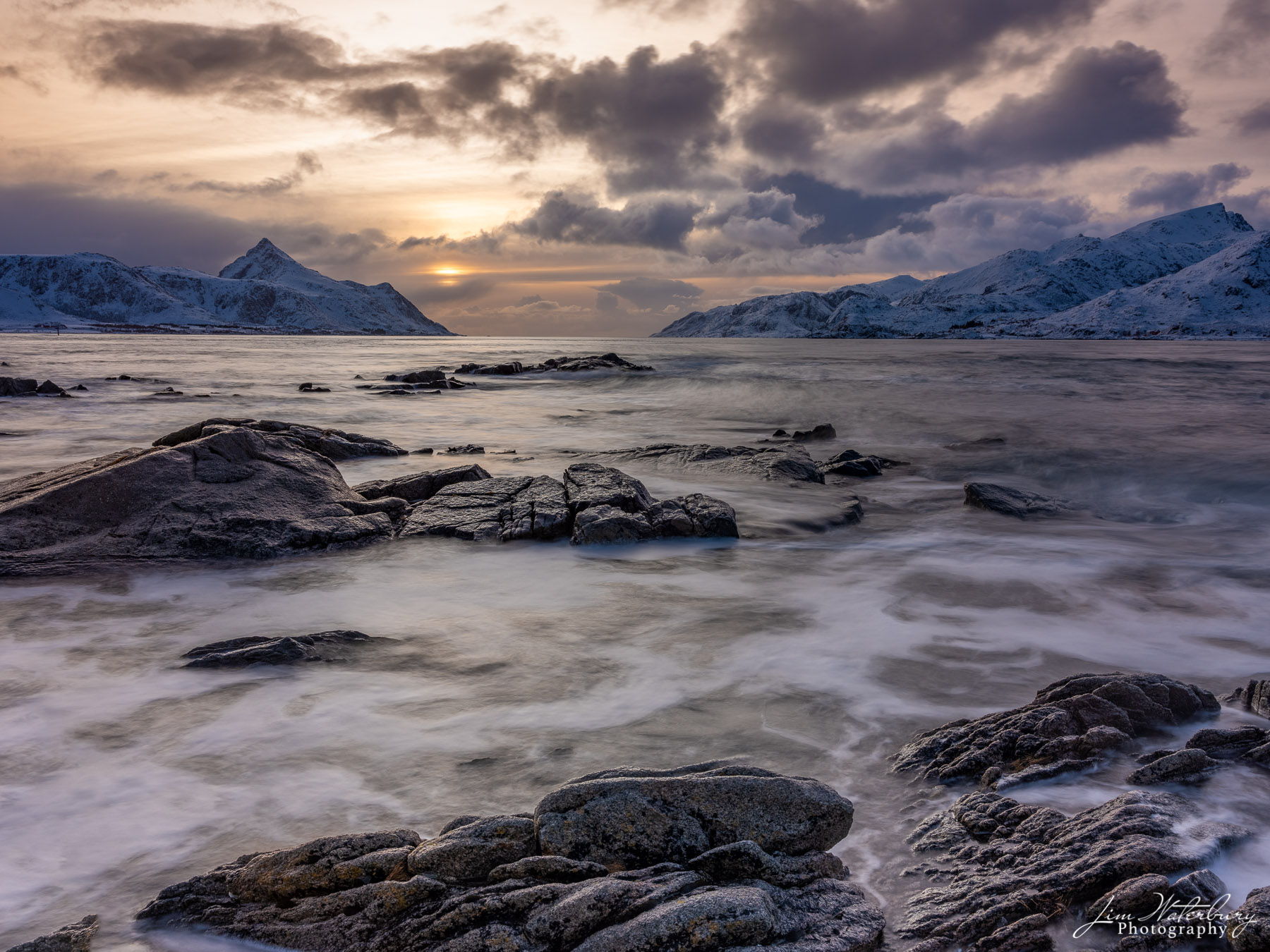 Layers of foam, rock, and clouds form a moody, late afternoon winter seascape across a fjord near Leknes in the Lofoten Islands...