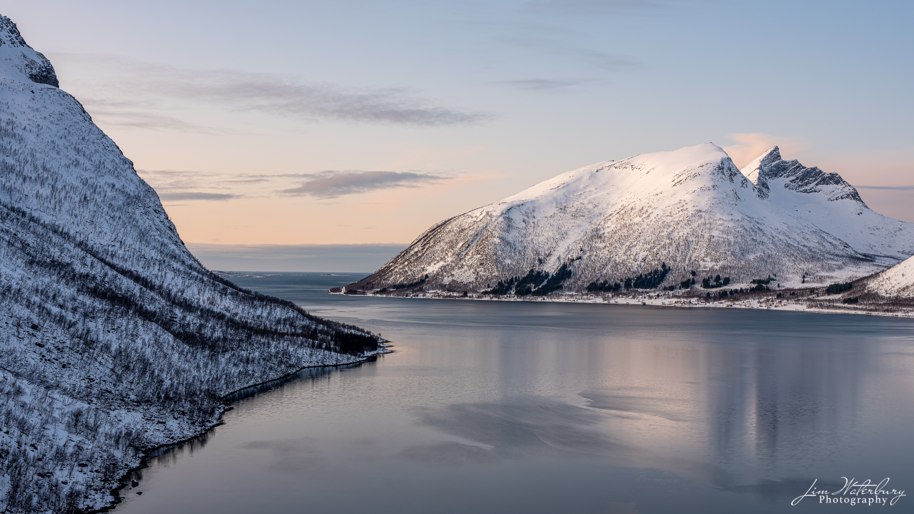 Soft evening light shines on the fjord at Bergsford, Senja, in the Lofoten Islands of Norway.
