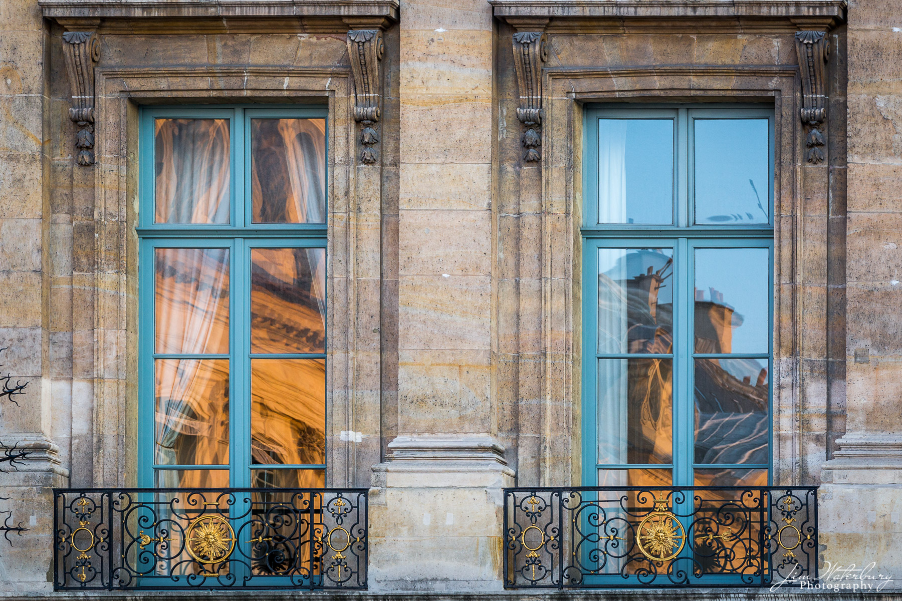 Windows in Place Vendome in central Paris reflect the golden light of sunset shining on the adjacent building.