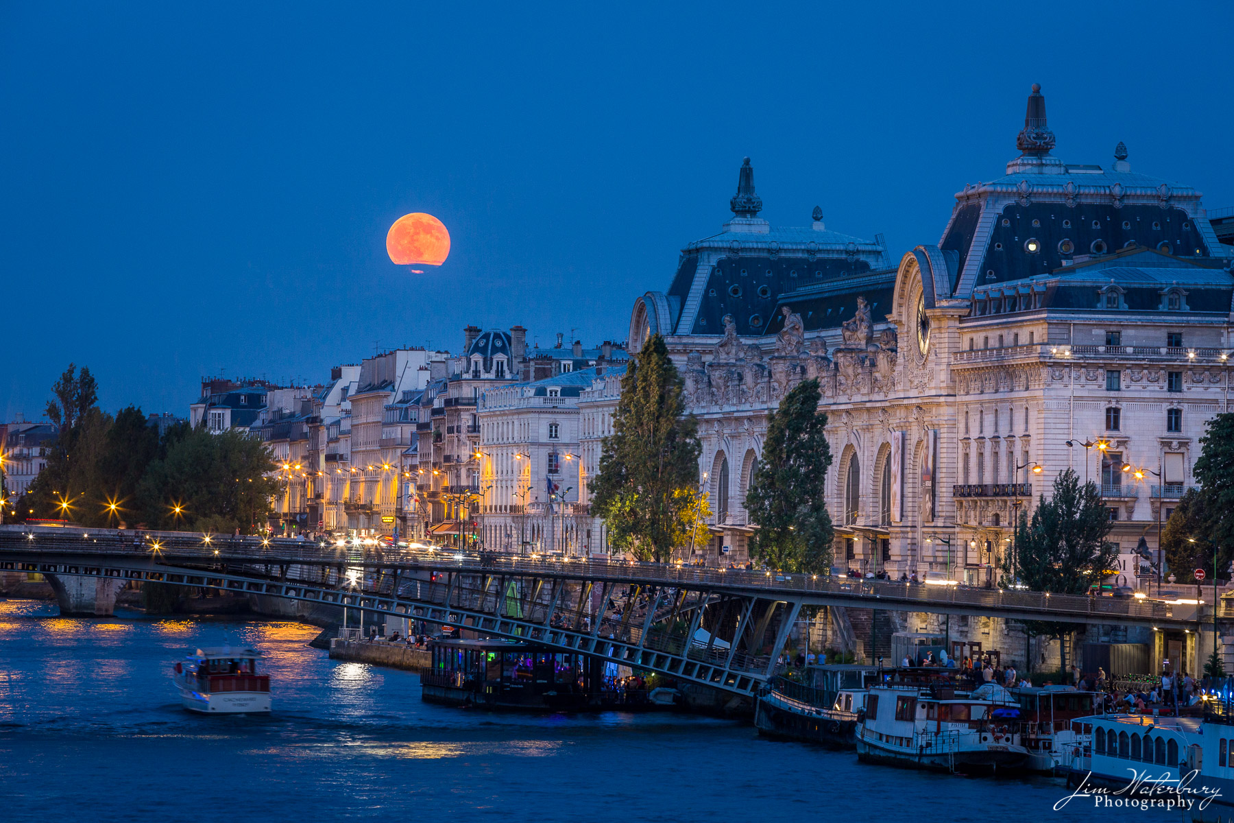 Full moon rises over the Musee d'Orsay in Paris just after sunset.