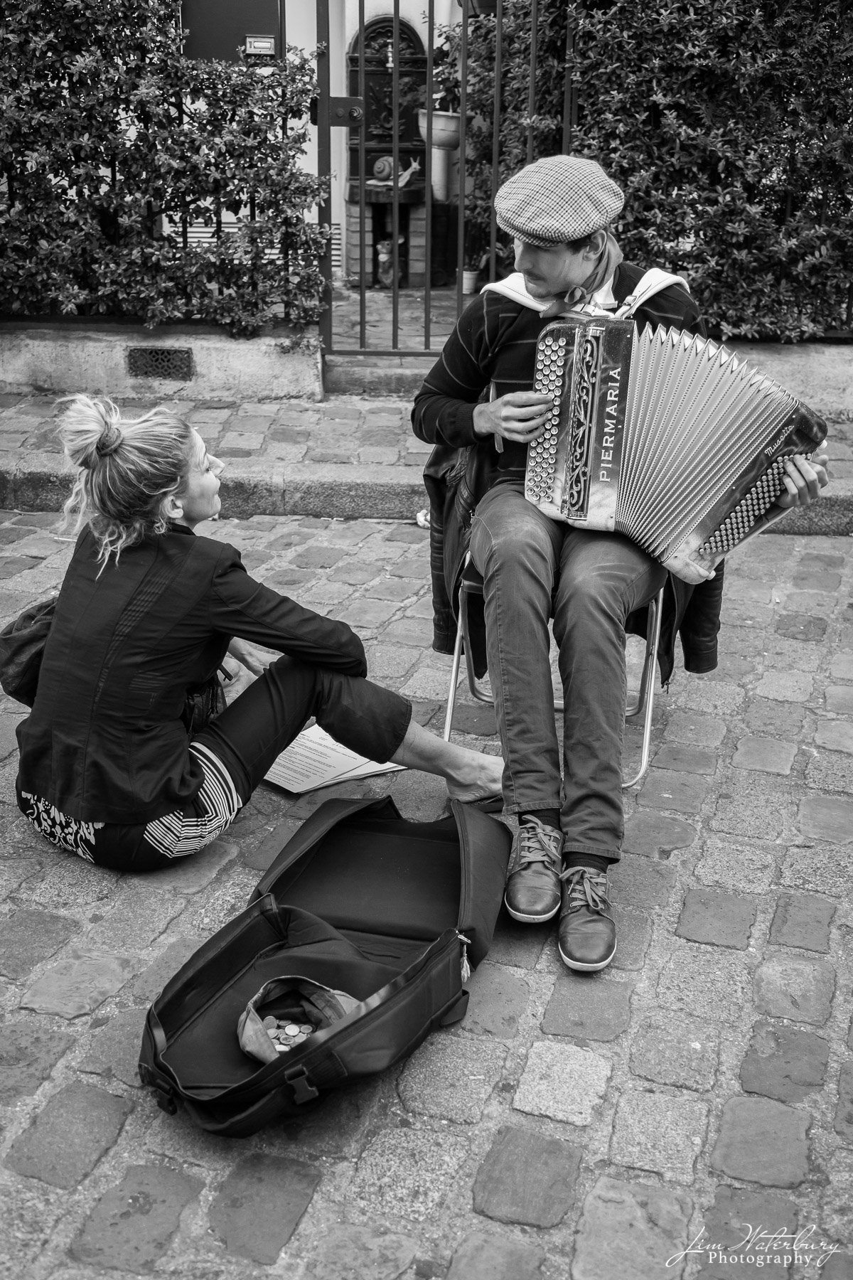An accordian player performs for a fan on the streets of Montmartre, Paris.  Black & white.
