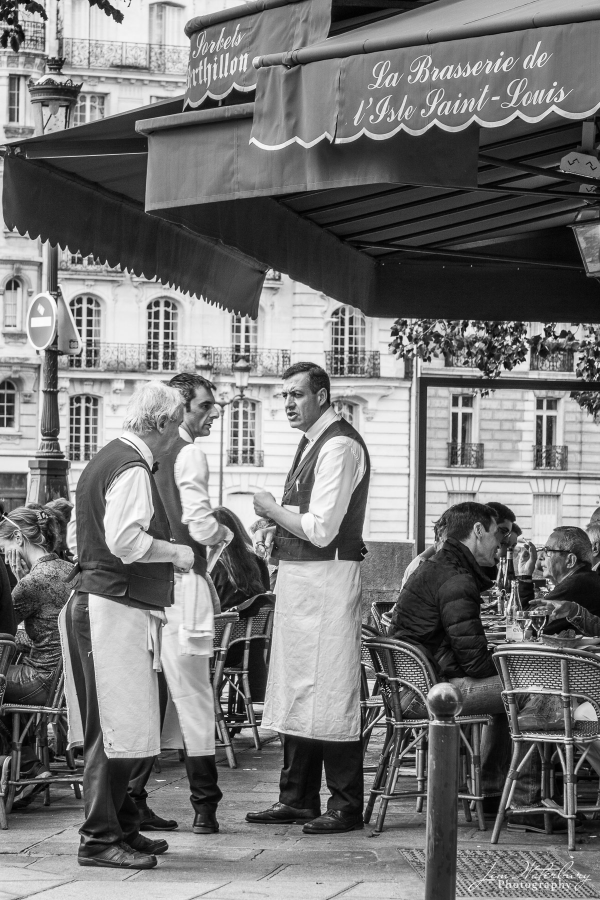 Waiters talk on the sidewalk in front of the Brasserie de l'Ile Saint-Louis, Paris. Black & white.