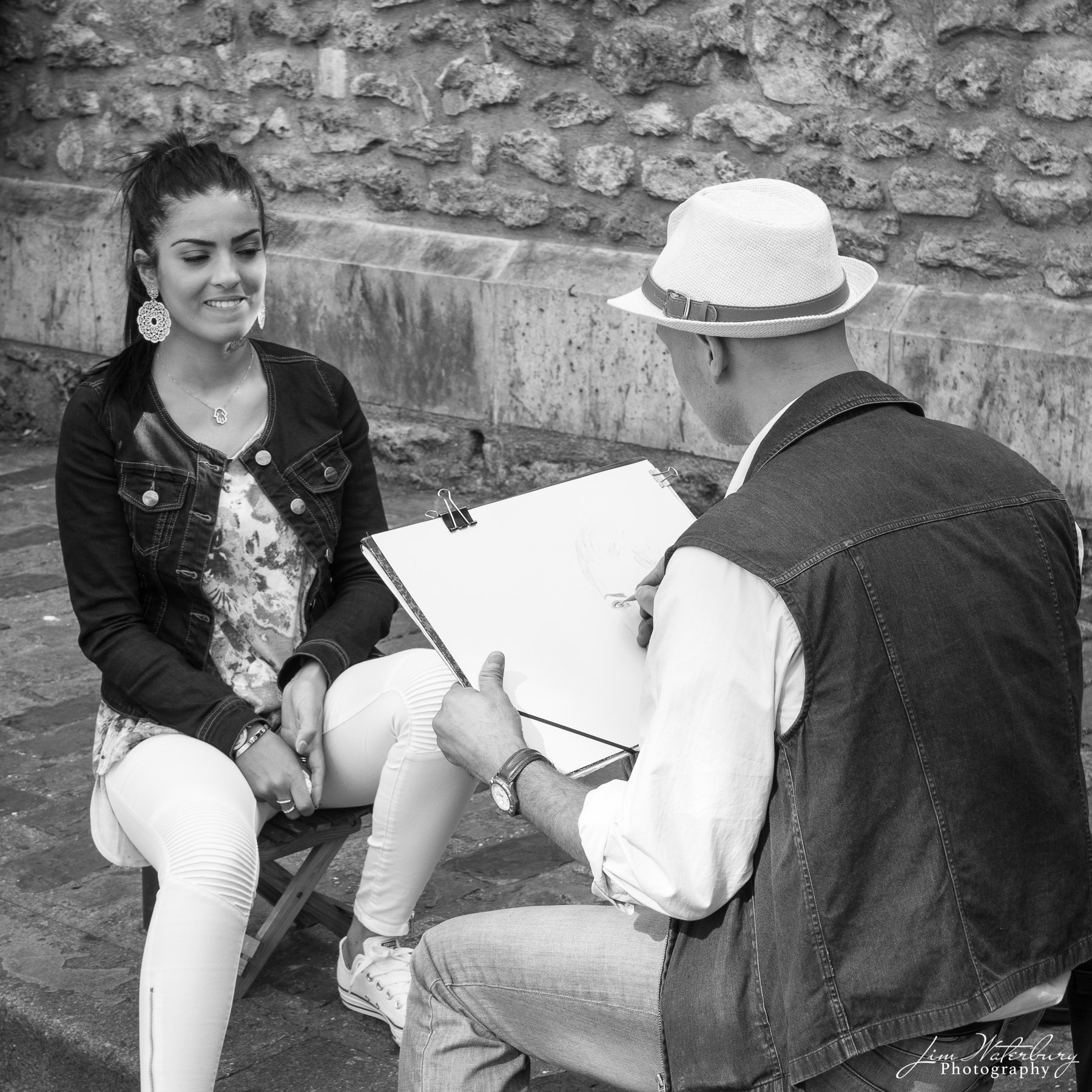 Artist in Montmartre, Paris, begins a charcoal drawing of a young woman.  Black & white.