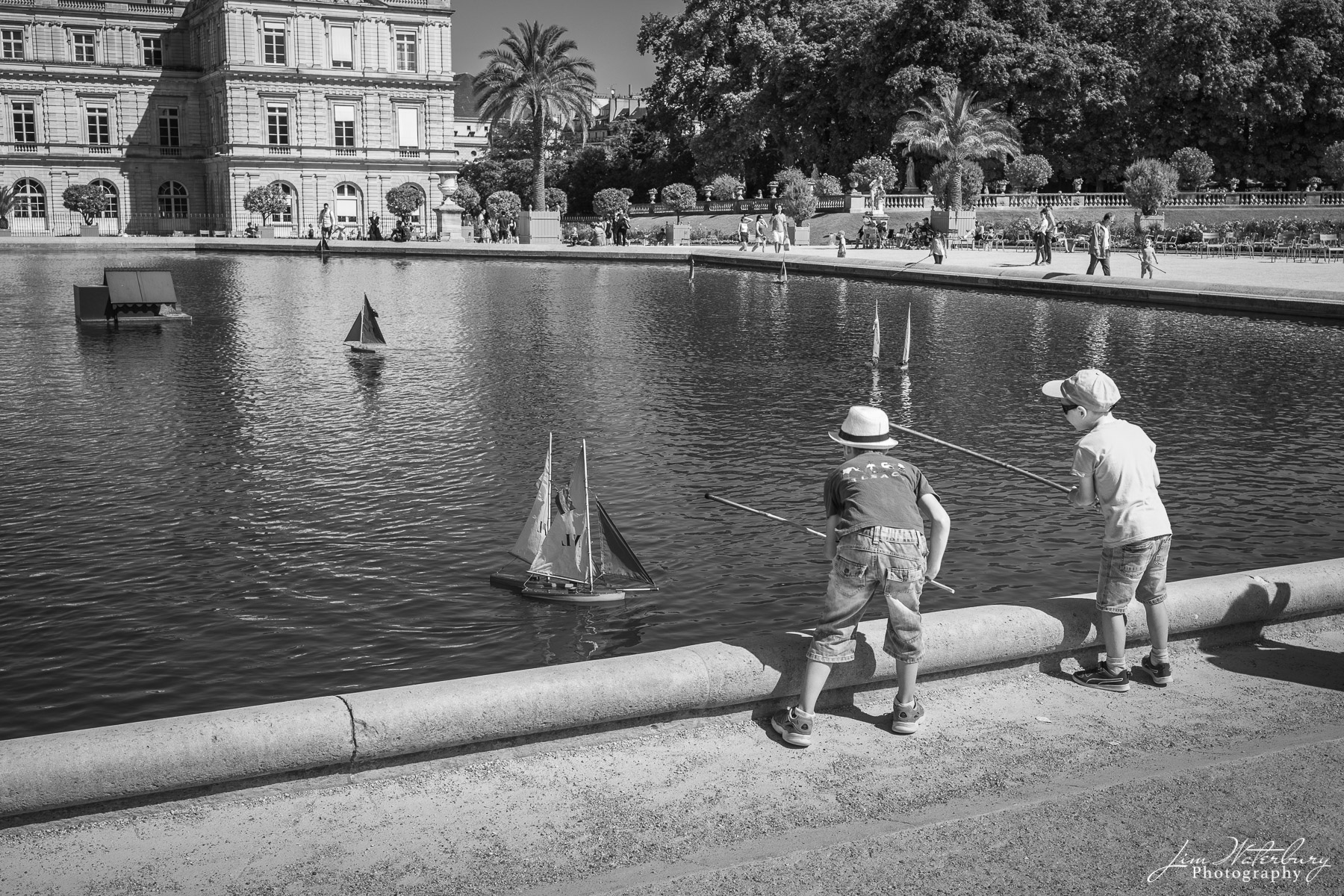 Two boys prepare to race their boats in the pond at the Luxembourg Gardens, Paris. Black & white.