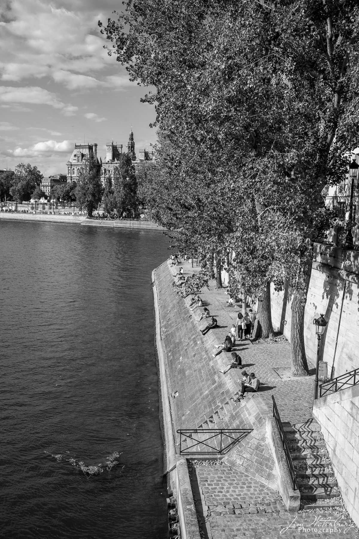 Students take advantage of a warm fall day to sit along the banks of the Seine.  Black & white.