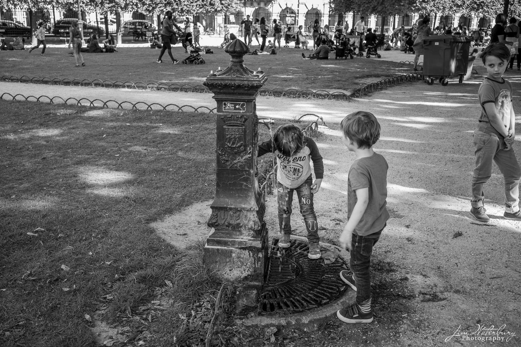Boys play in the fountain at Place Des Vosges, Paris, after school.  Black & white.